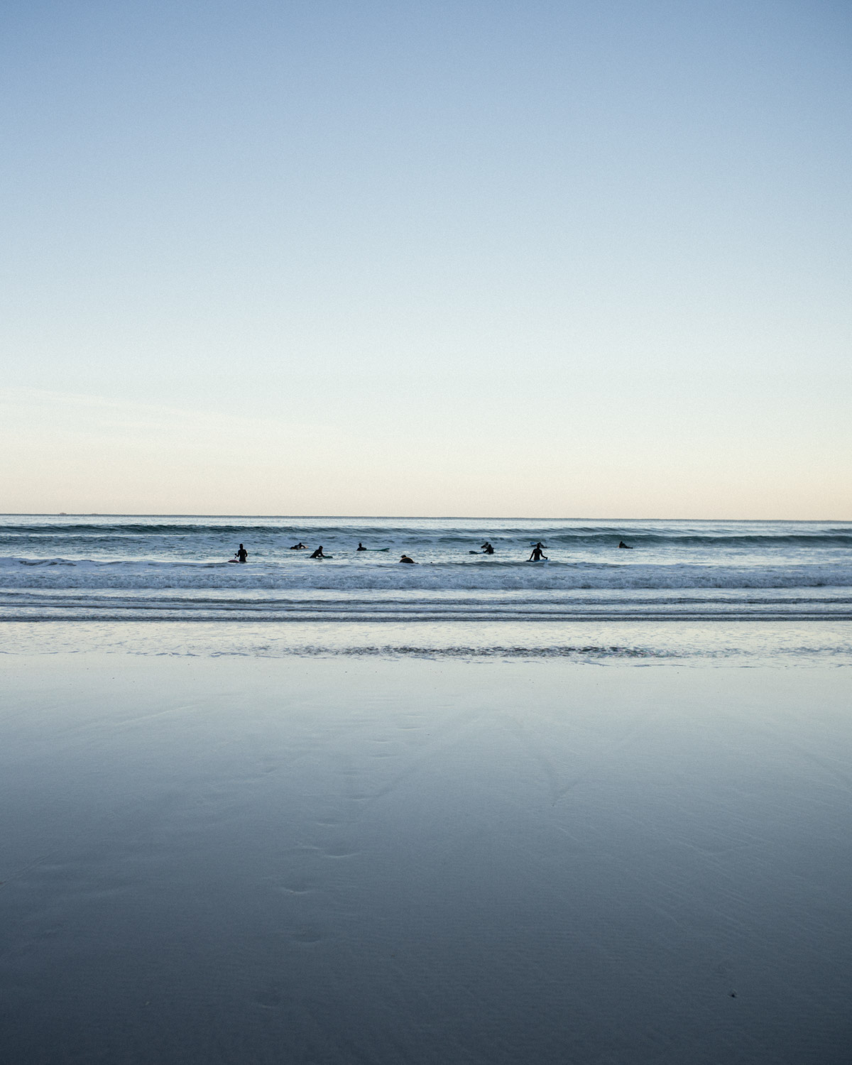 A group of amateur surfers are finishing a lesson on the spot of Flakstad