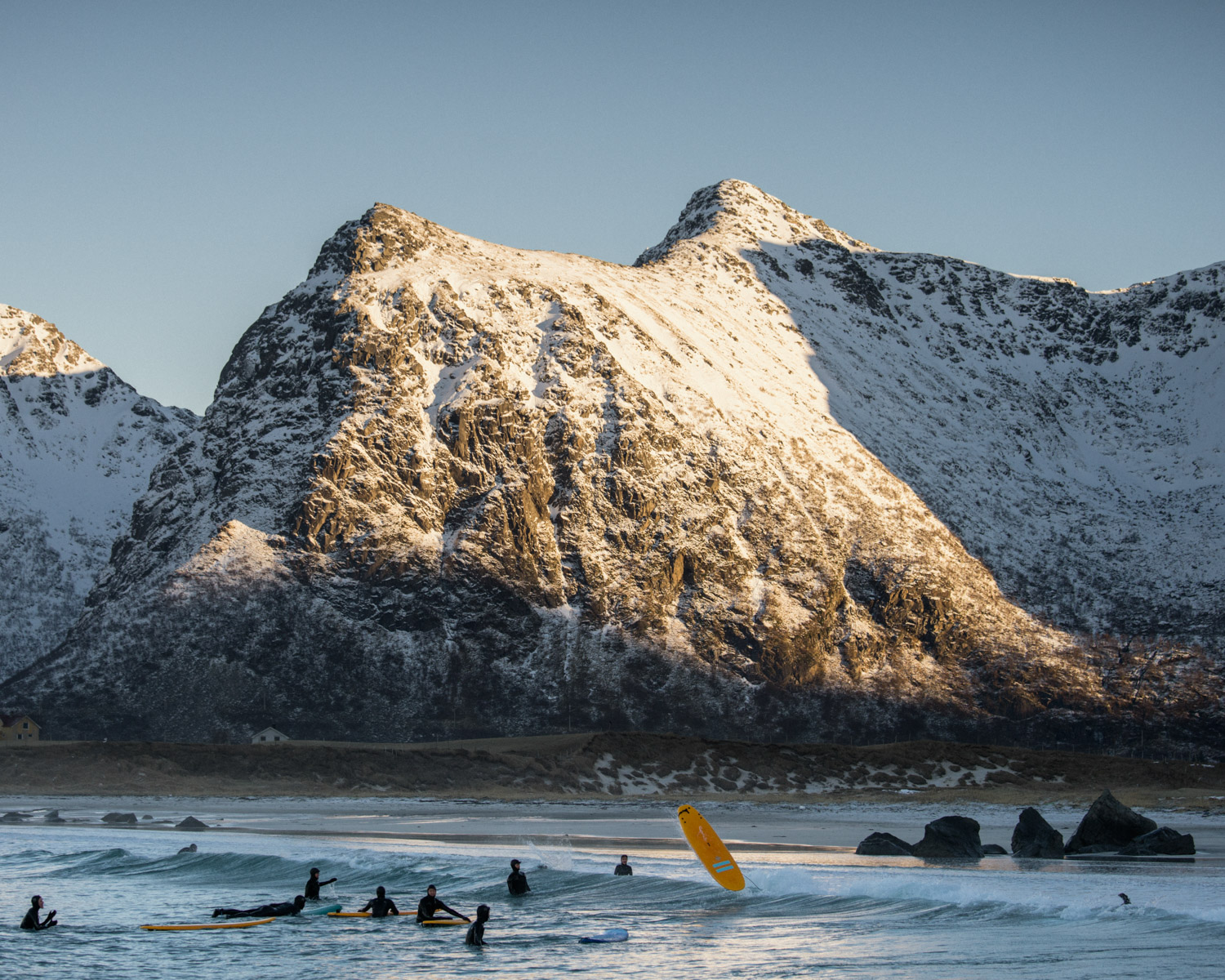 A group of visitor is learning to surf on the spot of Flakstad in the lofoten islands