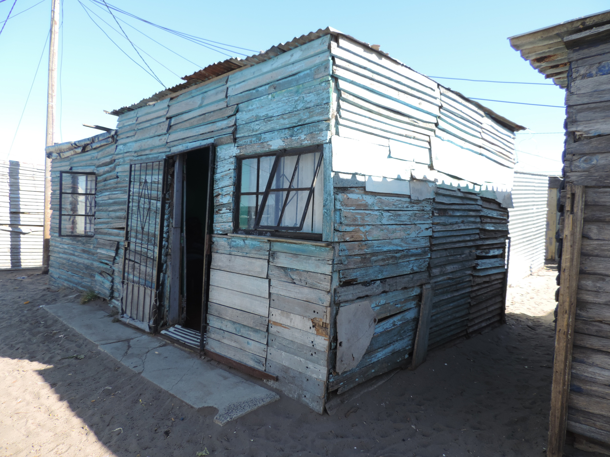 "Langa Township — photo of small wood-shingled shack with electrical wires hanging low overhead and another ""shack"" only two feet away."