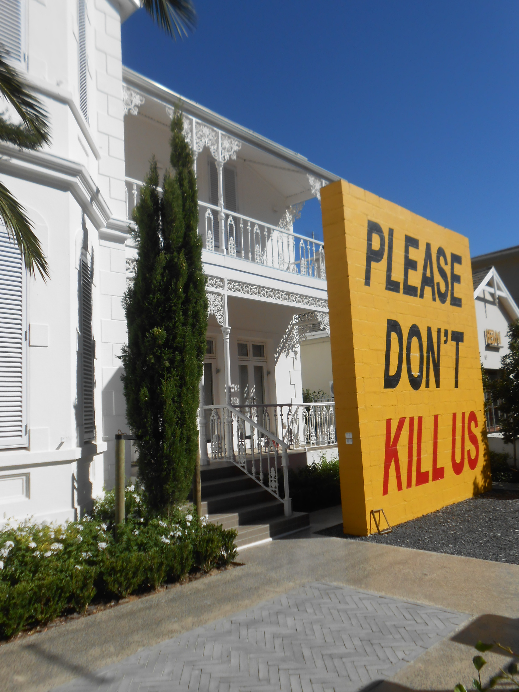 "Photo of a huge yellow sign with red writing that says ""PLease Don't Kill Us"". The sign is made of brick and formidable against the backdrop of an ornate hotel or residence."