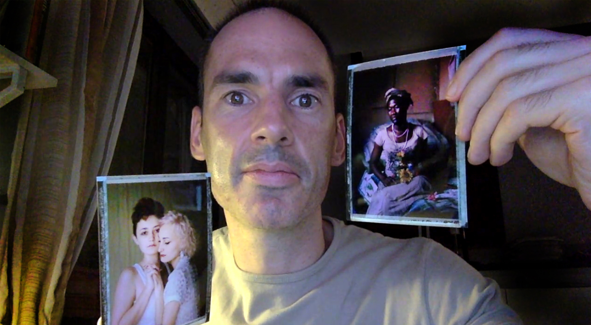 """Robin Hammond holds his images of D and O from Russia (viewer's left), and Tiwonge from Malawi (viewer's right) both part of his """"Where Love is Illegal"""" portfolio."""