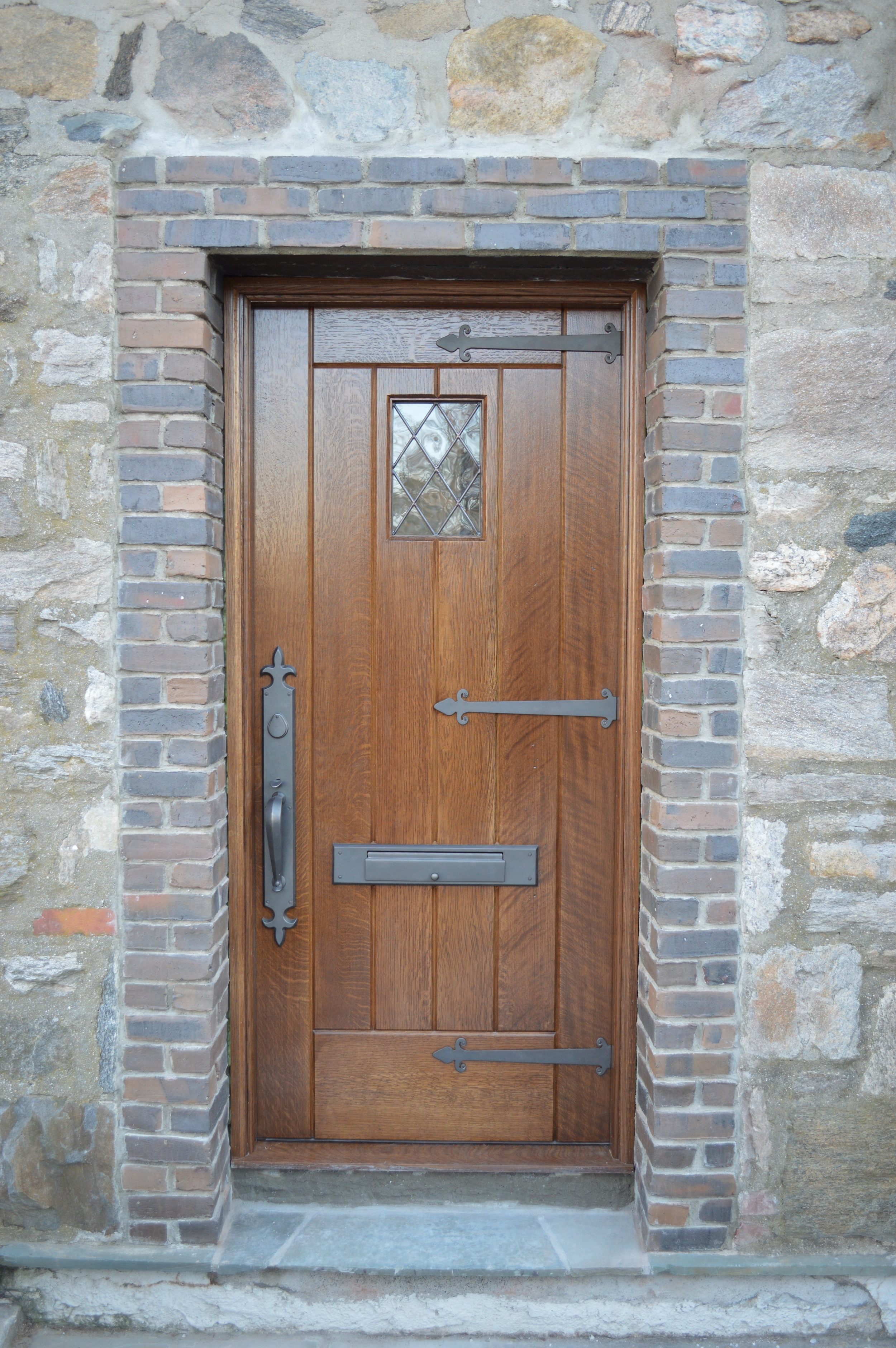 Solid rift & quartered white oak entry door. Everything is hand made, from the fabrication and staining of the door to the hammering of the hardware, to the blowing of the glass and setting of the led glass inlay.