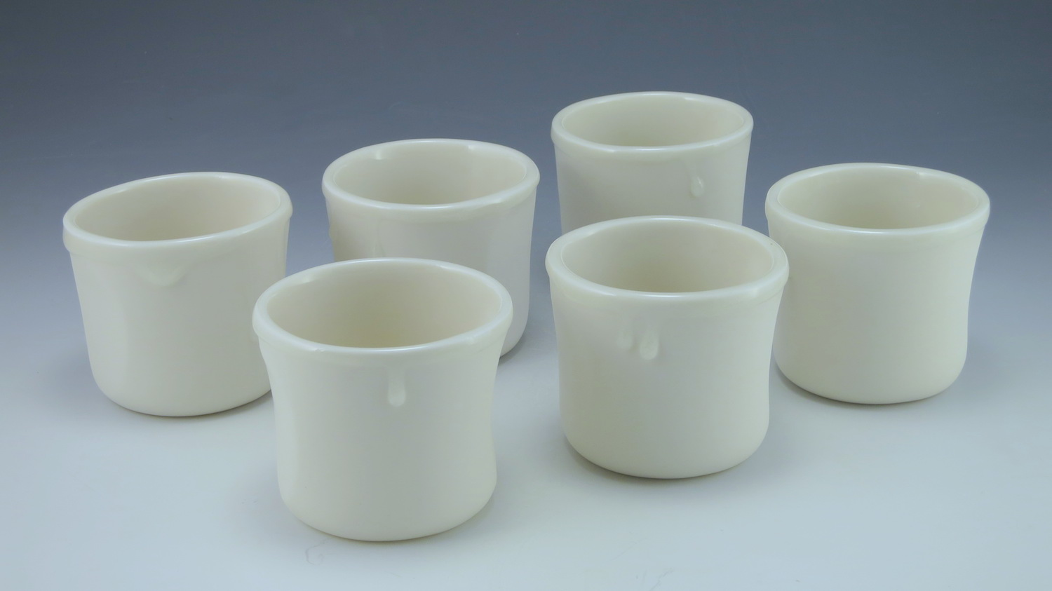 WHITE WHISKY    A pure white 5oz cup, with a clear juicy glaze that slops over the rim and runs in heavy drips down the side.  Thumb and forefinger cut outs help the cup nestle in your hand, as does the little tuck on the underside of the cup.  Made from my purest porcelain slip, these cups are sanded at every stage and their smooth, silky surface caresses your fingers, while the glaze drips give them something to play with.     Made with late night whiskey sessions in mind.