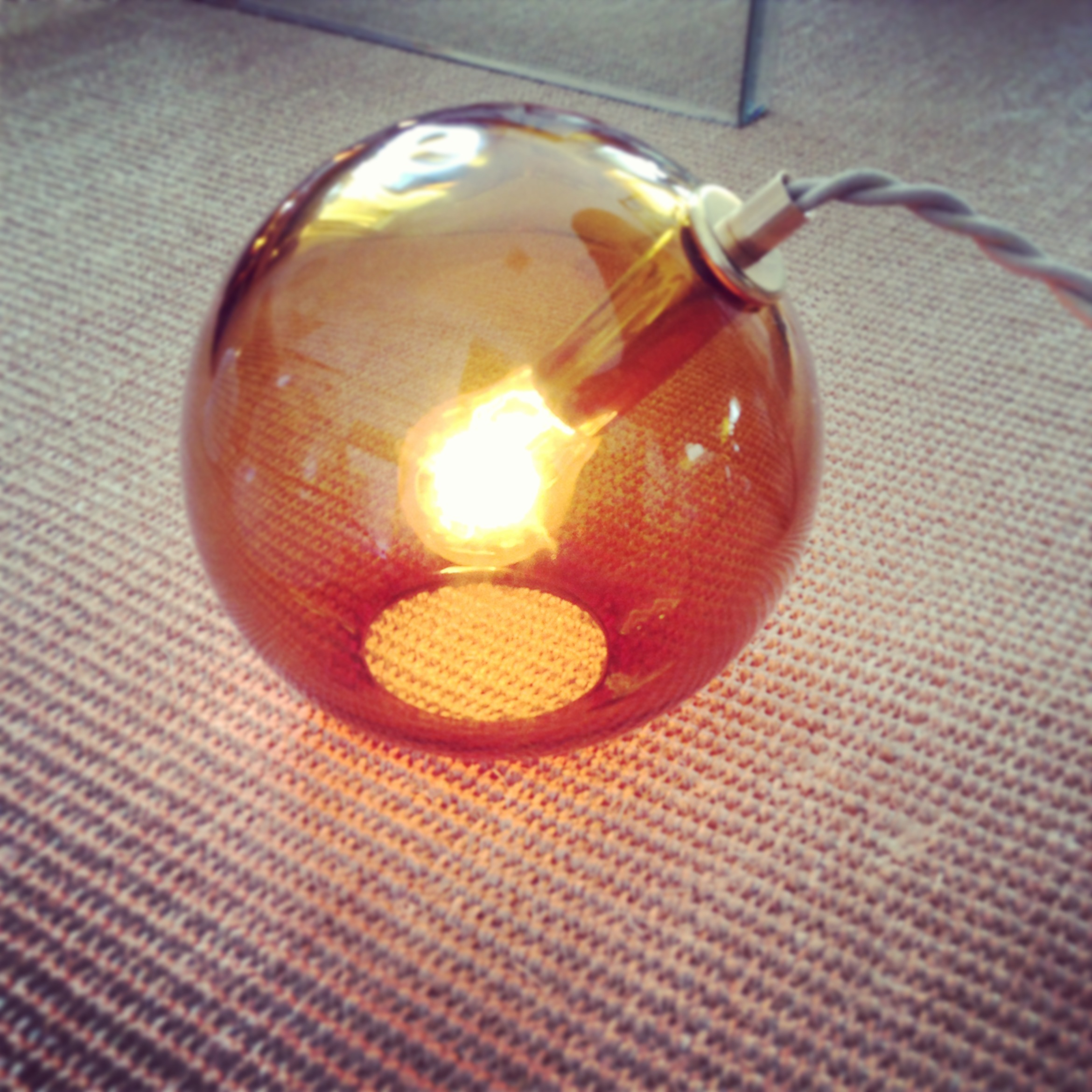 BUBBLE LAMP  an imperfect sphere. like a lopsided bubble.   materials: hand blown glass, custom brass fittings, cloth covered electrical cord