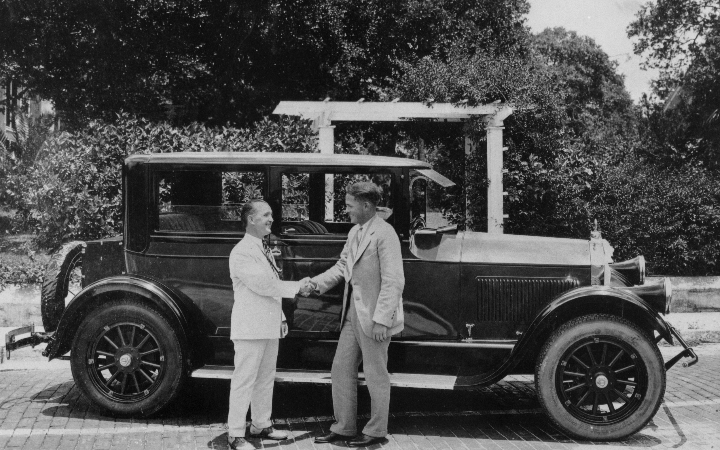 Bobby Jones accepts the gift of a new Pierce-Arrow Series 80 Coach from Jules Brazil on behalf of the City of Sarasota and the Chamber of Commerce in celebration of Bobby Jones' 1926 Open Championship at Royal Lytham & St. Annes Golf Club. Jones drove the car back home to Atlanta following this train trip to Sarasota. Photograph Courtesy of Sarasota County Historical Resources.