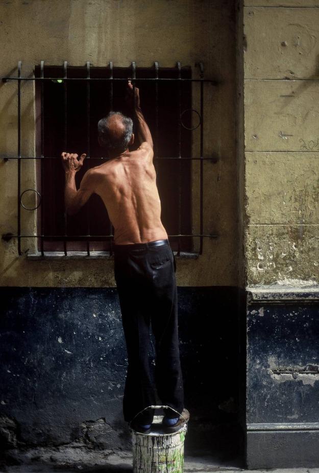 man repairing window old havana cuba