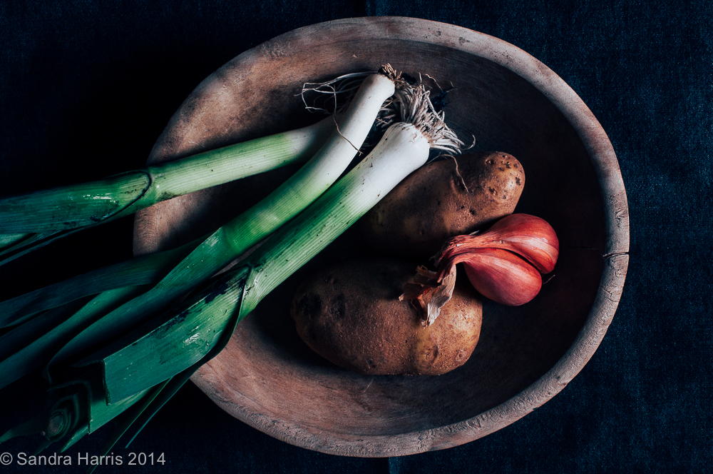 leeks, potatoes and shallots in an old wooden bowl - Sandra Harris
