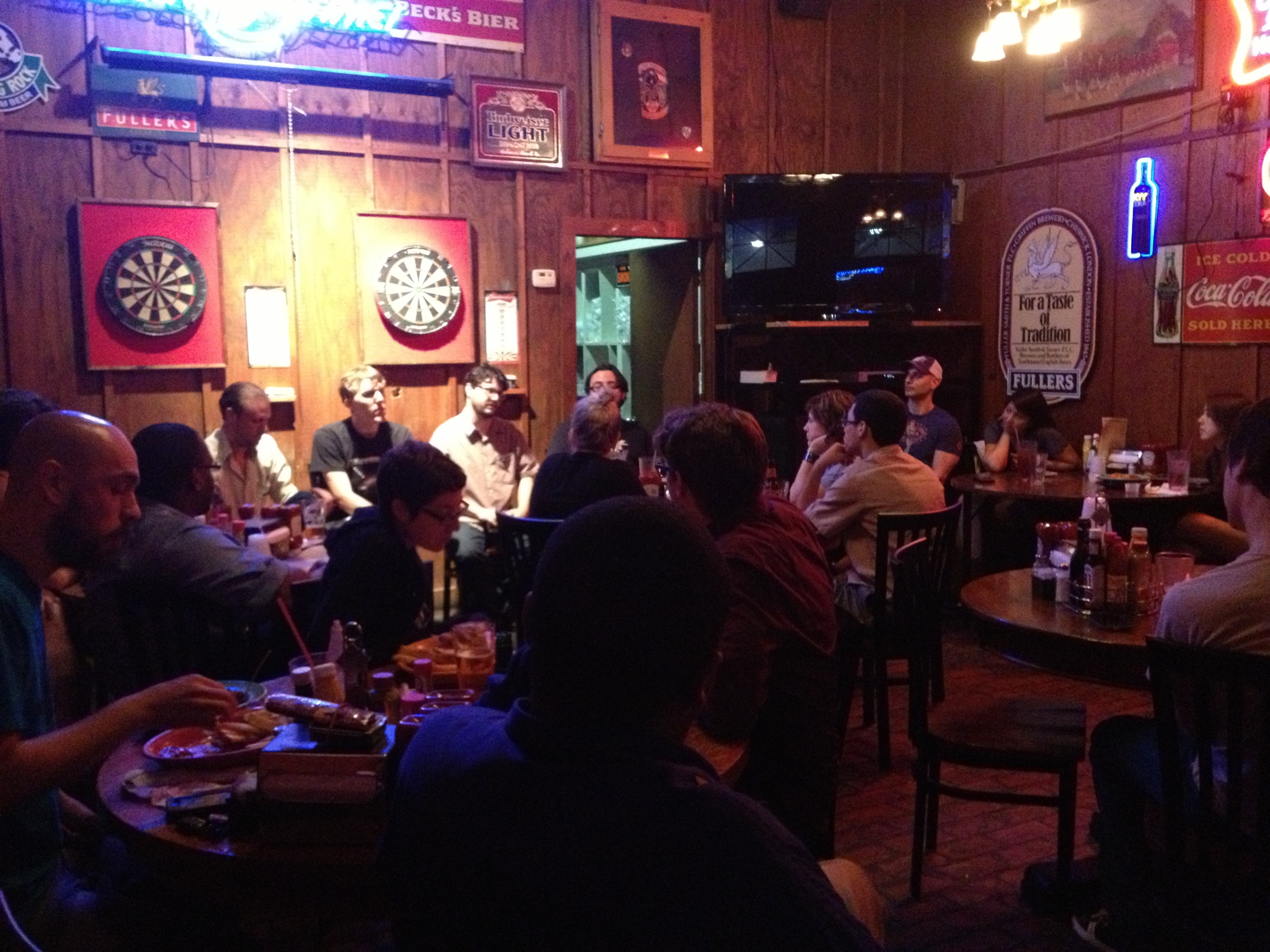 The members of New Puppet Order (seated beneath the dart boards) at Manuel's Tavern.