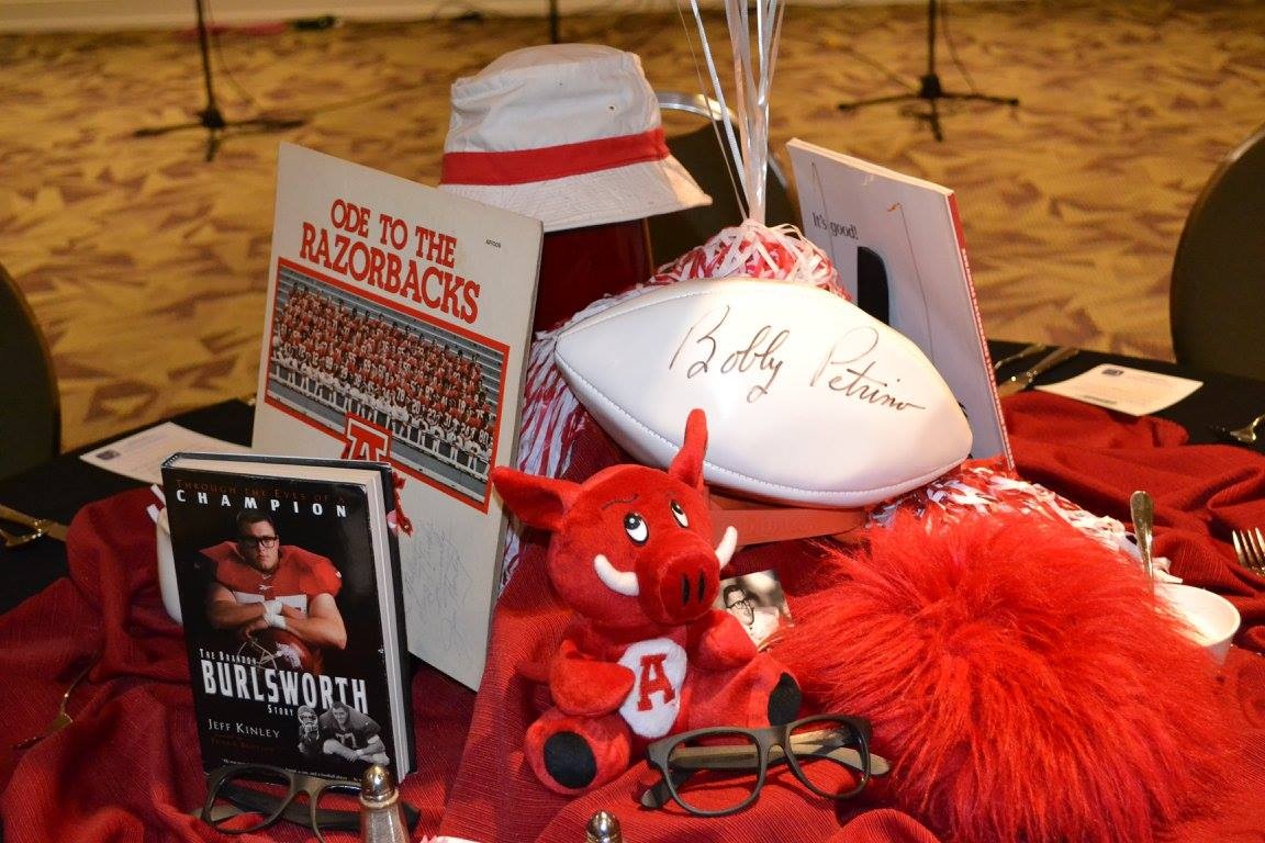 "The date of the event coincidentally was the five year anniversary of the motorcycle incident of the coach who signed the above football. If you look closely at the ""Ode to the Razorbacks"" vinyl record, one of the players is wearing #12. He was the first and only player to wear the number since 1950. The team's only other retired number is Burlsworth's #77, which the school retired on the first home game after his death in 1999."
