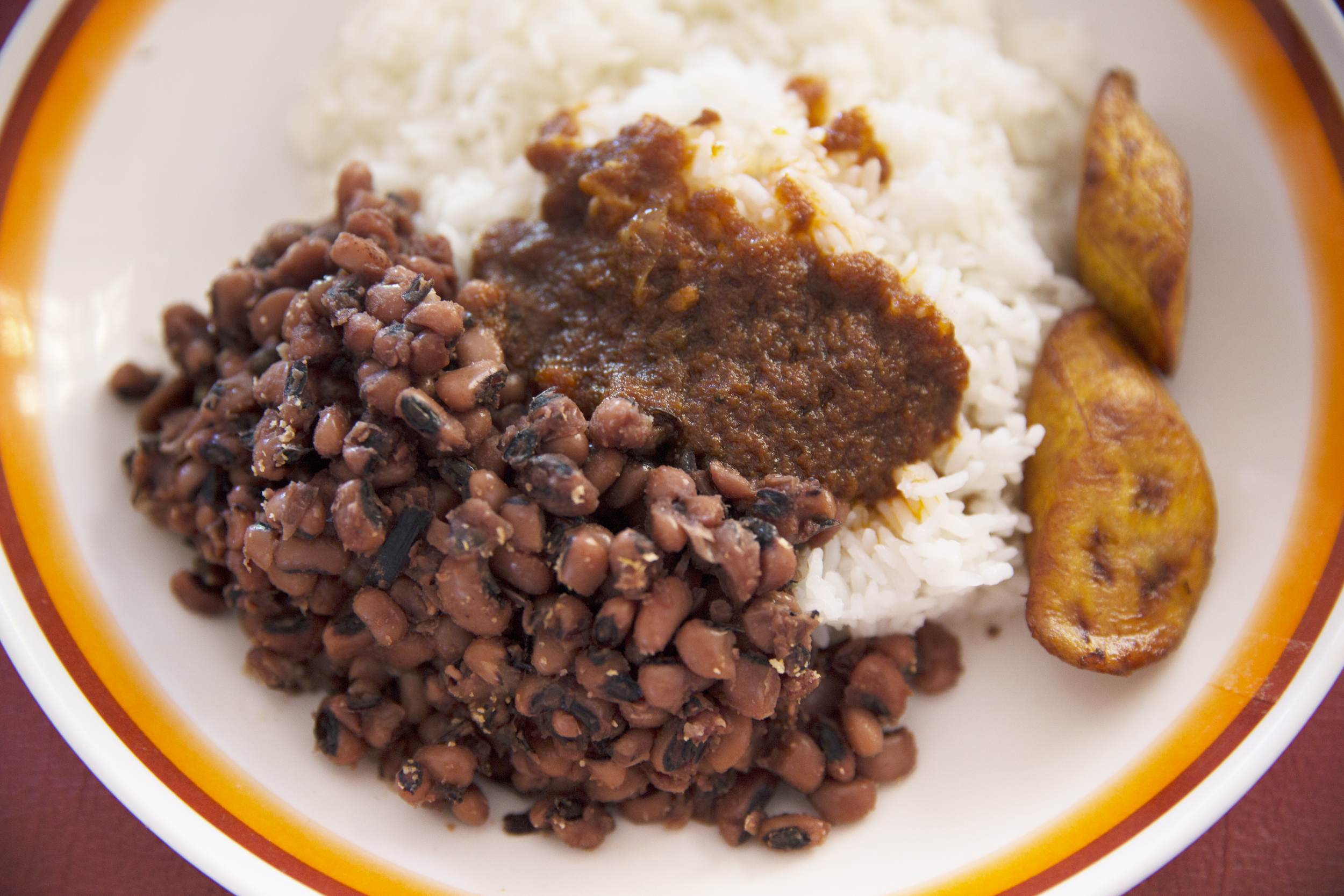 My meal of rice, beans, fried plantains,and a spicy sauce.