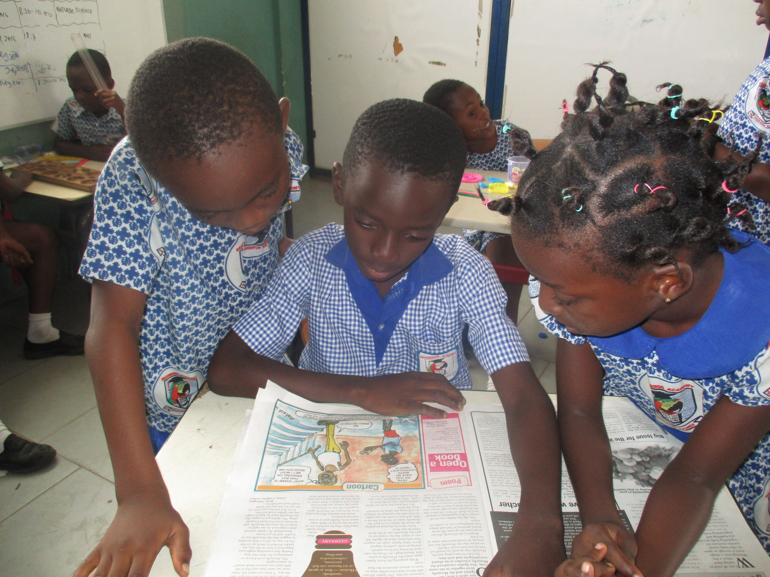"Students study a ""graphic"" (newspaper), by  Alberta, Christiana, and Ruth, Class 6."