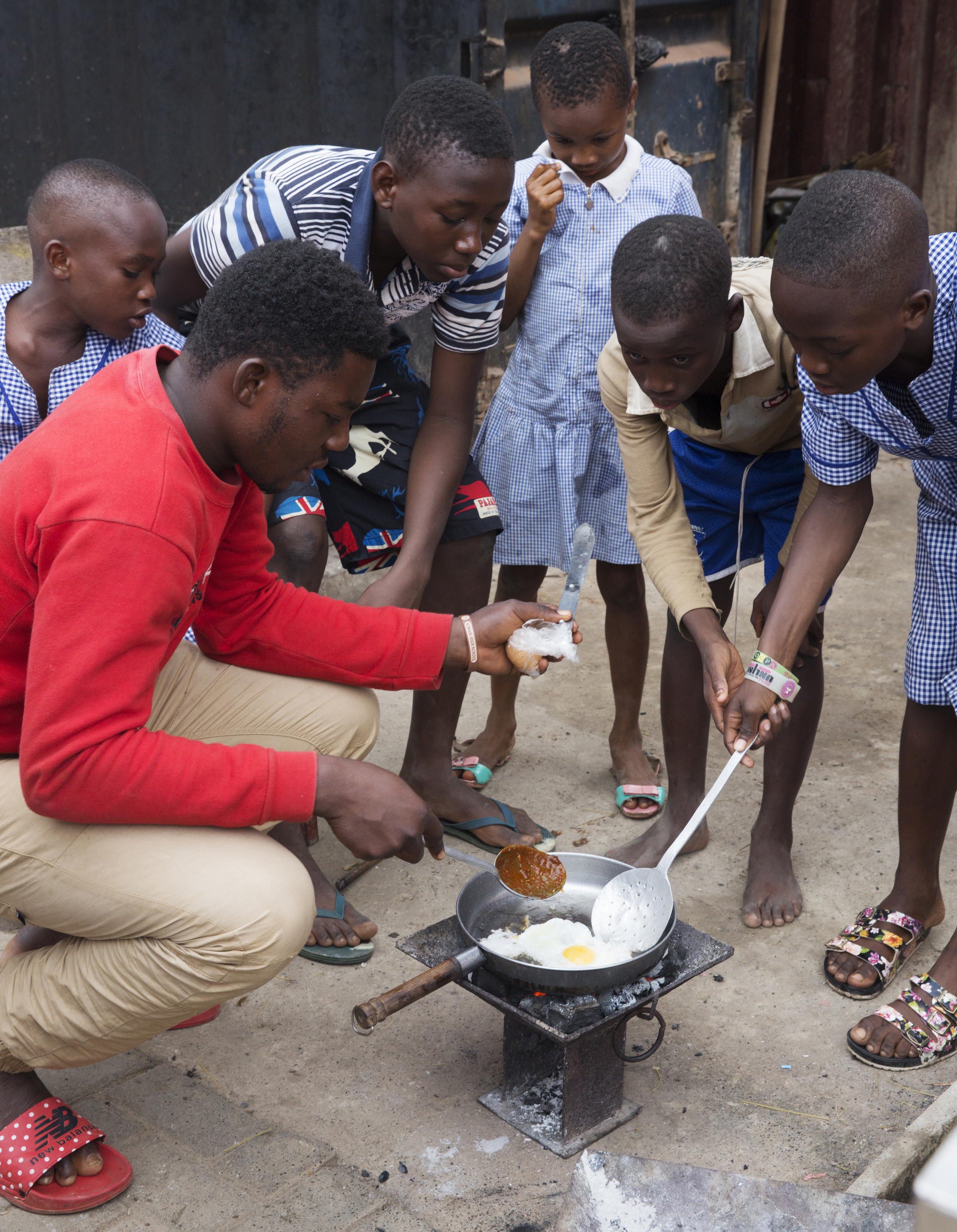 Sir Dennis helps the kids to fry the eggs that they will later chop up and add to their spaghetti.