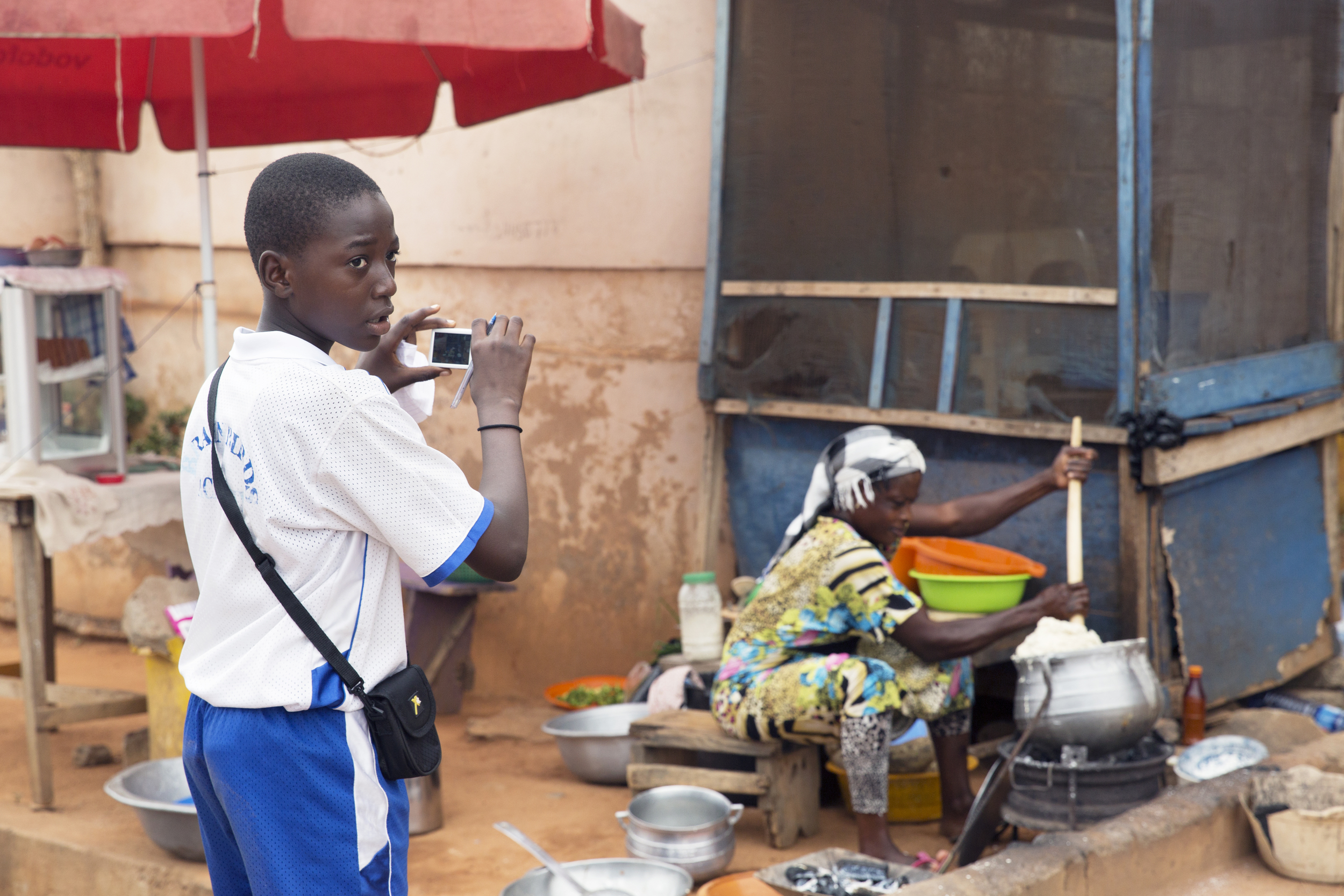 Hakeem photographs a woman making banku across from the school.