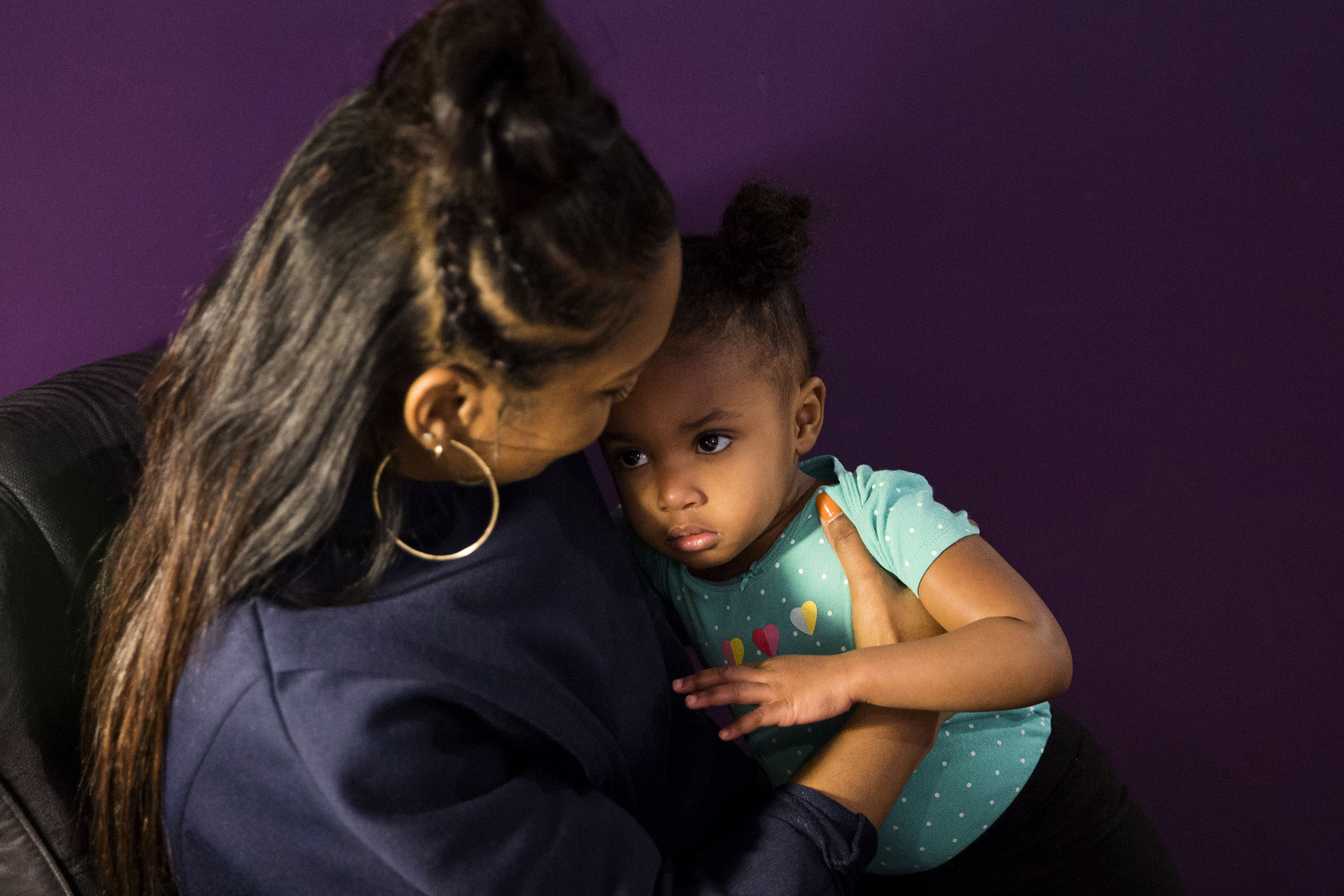 "Midwife Asasiya Muhammad (left) hugs two year old Annalulu Ndanu in her office at Inner Circle Midwifery on February 9, 2019. Muhammad delivered Ndanu two years ago and is now affectionately referred to as ""Auntie Asasiya"" by Ndanu and her siblings. (Shot on assignment for WHYY)"