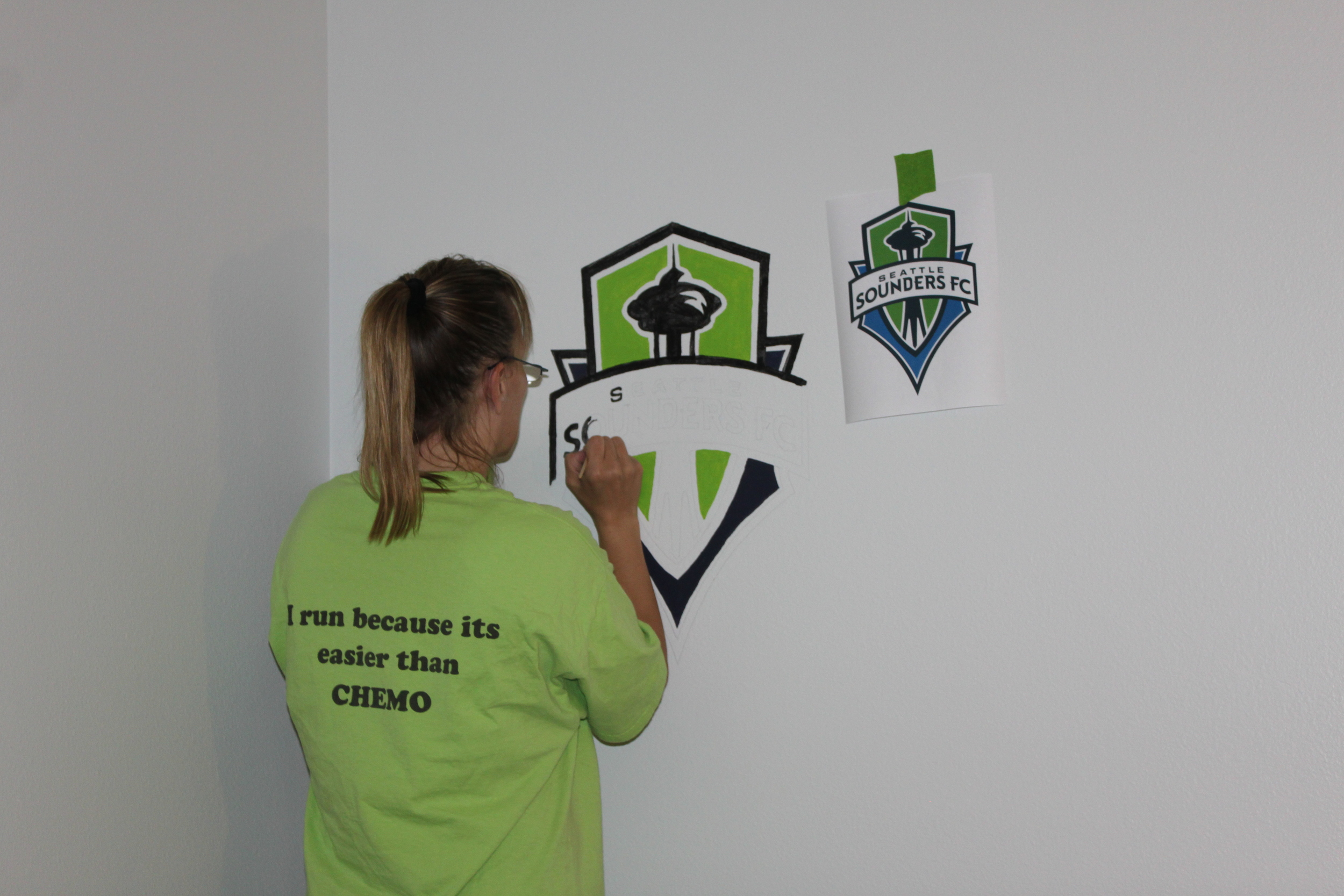 Doreen painting the Sounders logo on the wall.