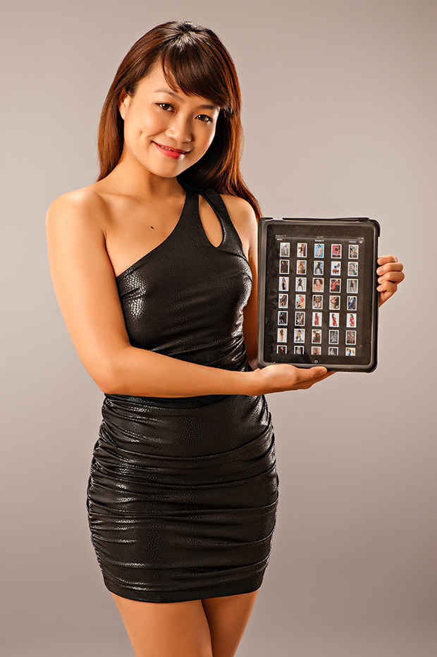 Model Stella Seet displaying a folder of vertical portraits of models wearing dresses.