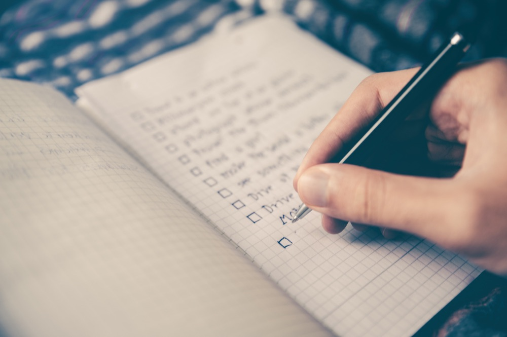 A photo of a person holding a pen and writing a checklist on a notebook. Photo by  Glenn Carstens-Peters on  Unsplash