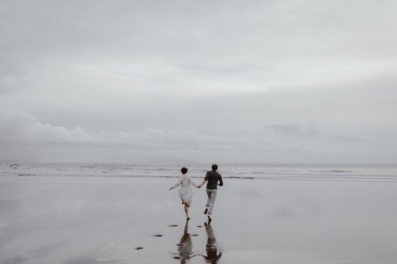 A couple runs on the sand at their Oregon coast engagement session