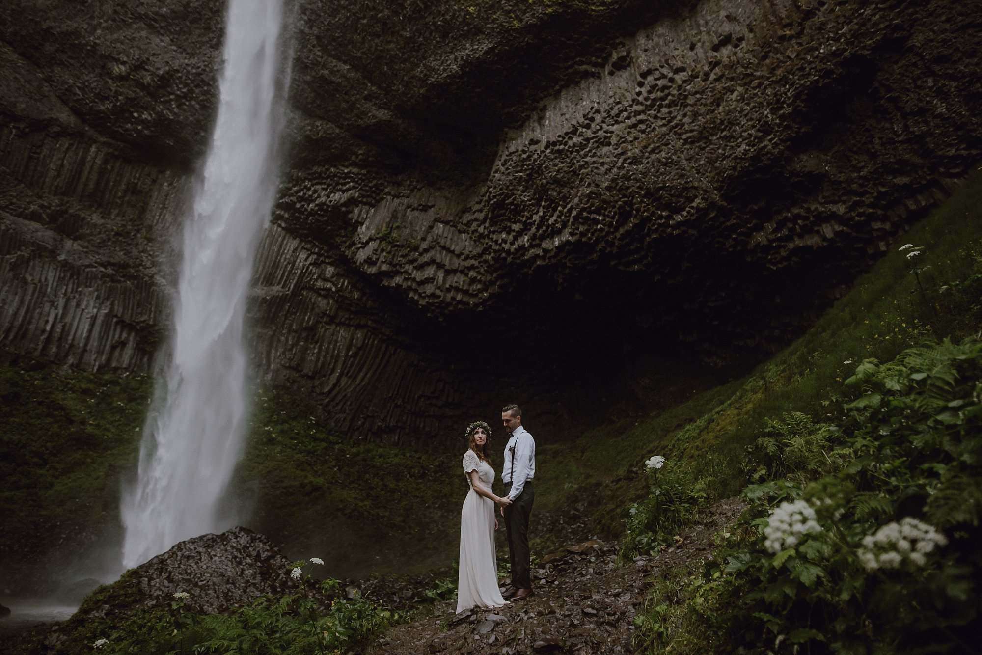 A photo of a bride and groom in front of a waterfall.