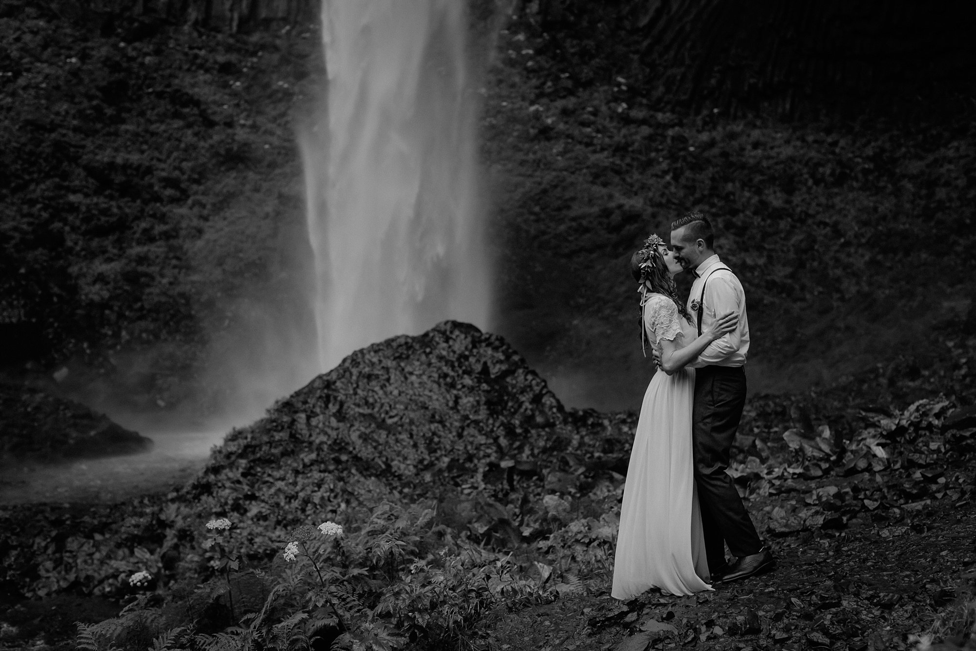 The bride and groom kiss in front of a waterfall.