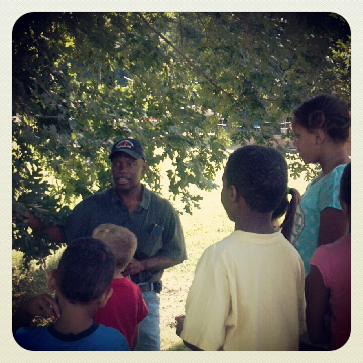 Alton Perry takes youth on a nature walk, discussing with the kids how trees are living organisms just as they are.
