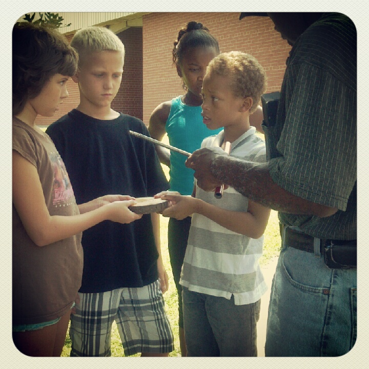 """Mr. Perry shows the kids a """"tree cookie,"""" a tool used by the forestry service to determine the age of a tree."""