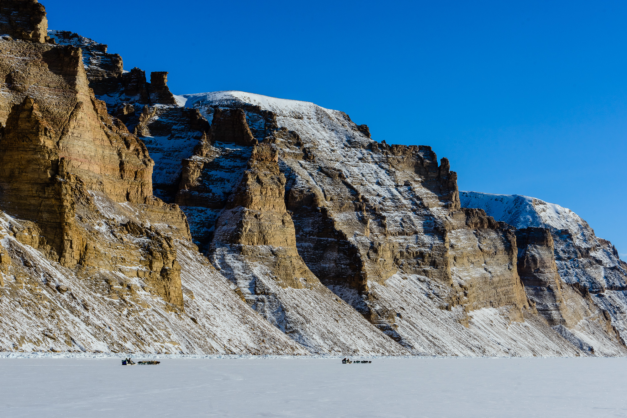 Inuit Dogsleds Travelling the Sea Ice Beneath Colorful Cliffs