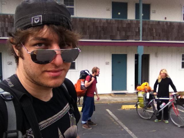 Amirkhani photographs himself at a motel while Sam Rossi Harries and Maya talk in the background. Courtesy Justin Amirkhani