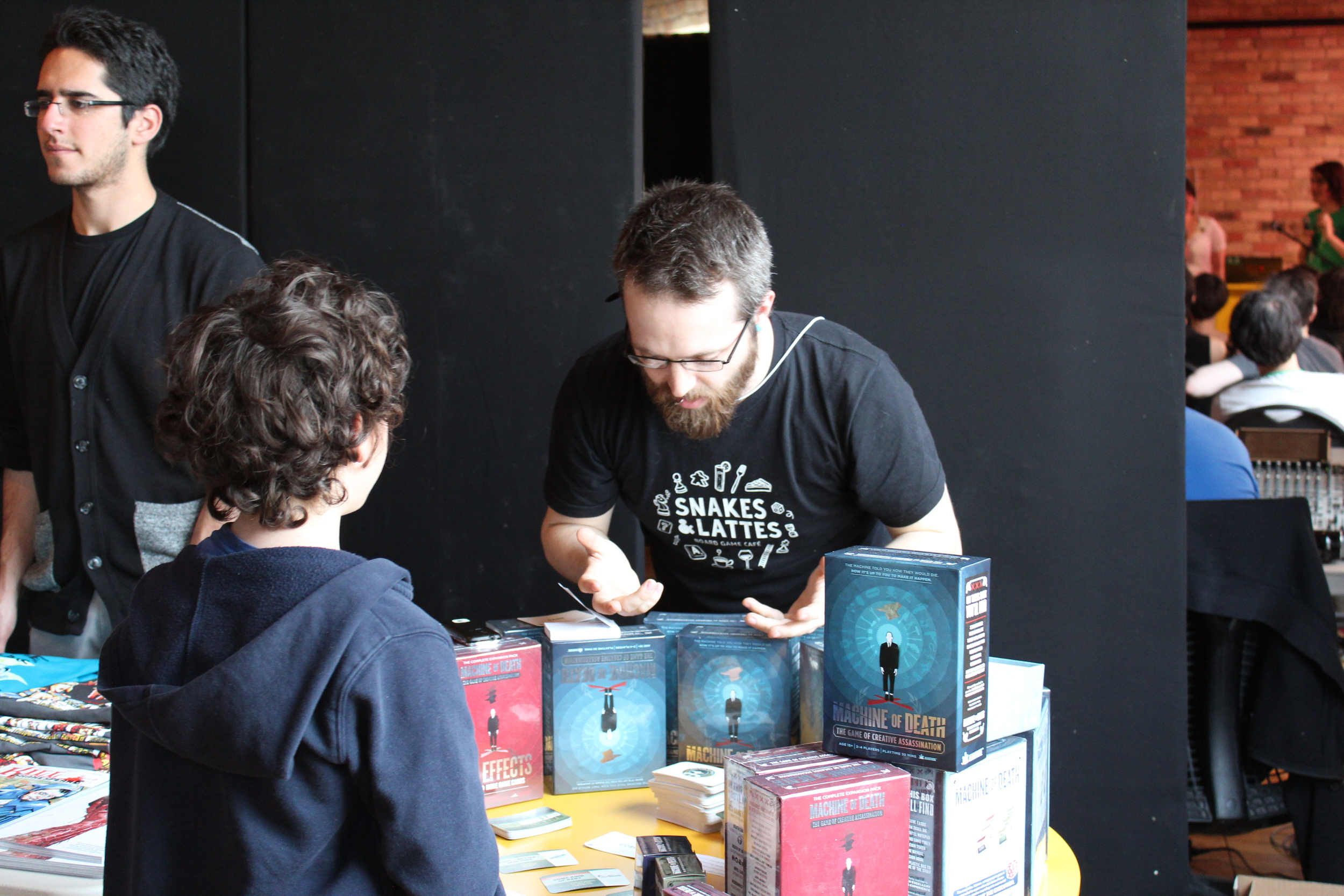 A volunteer from Snakes and Lattes shows off a version of the Machine of Death card game, based on Ryan North's anthology book of the same name.