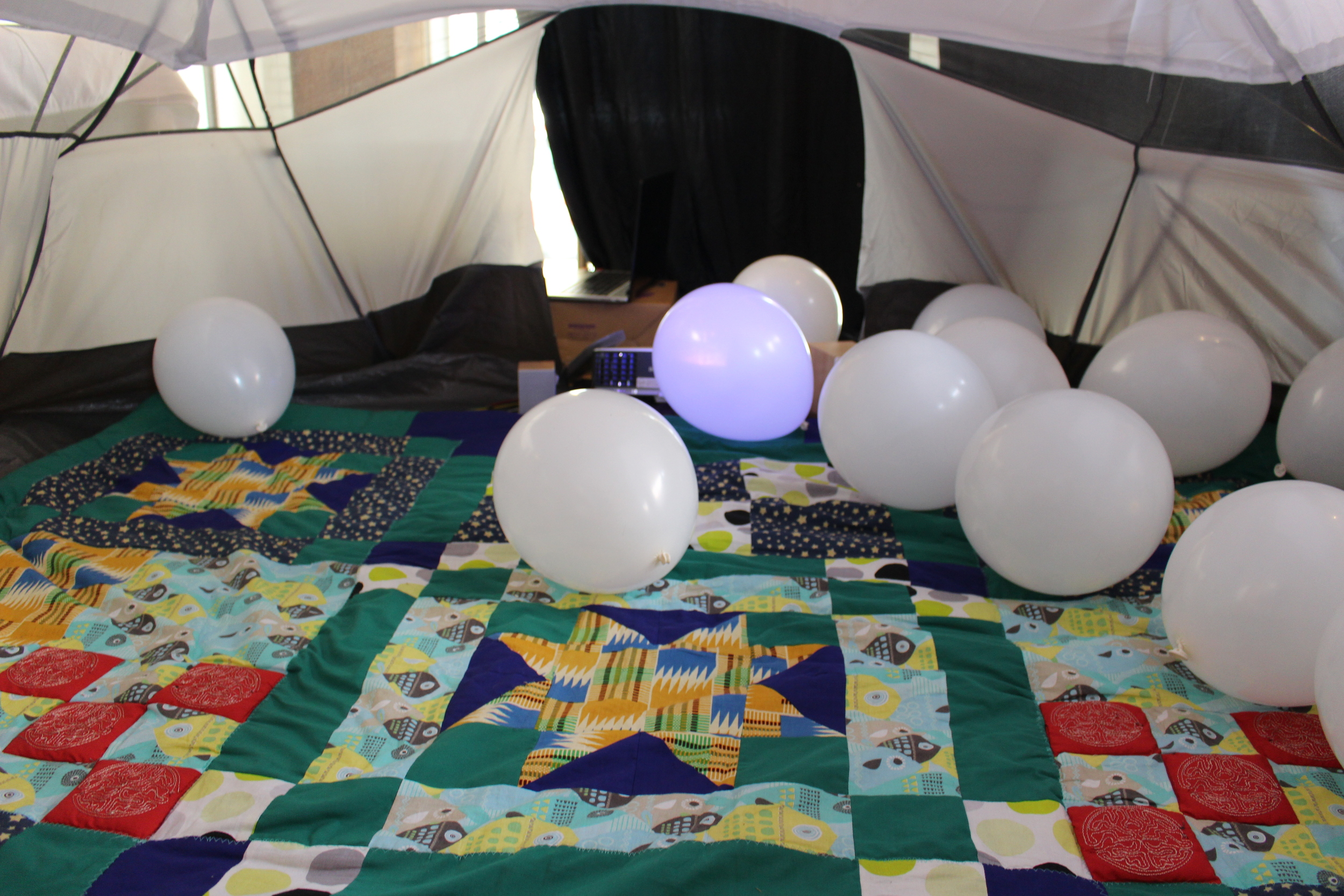 Mouffe, the interactive tent, where the quilt is the controller for a screen projected onto the tent's ceiling
