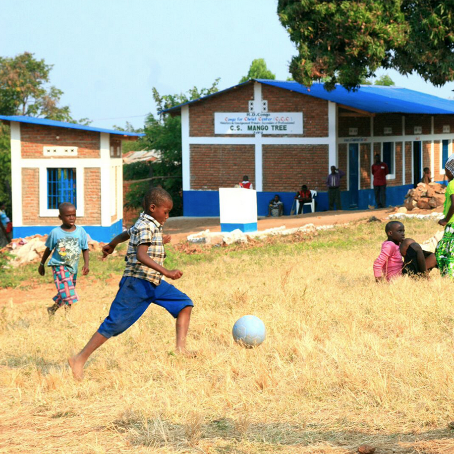 children playing soccer outside of Mango Tree School in eastern DR Congo