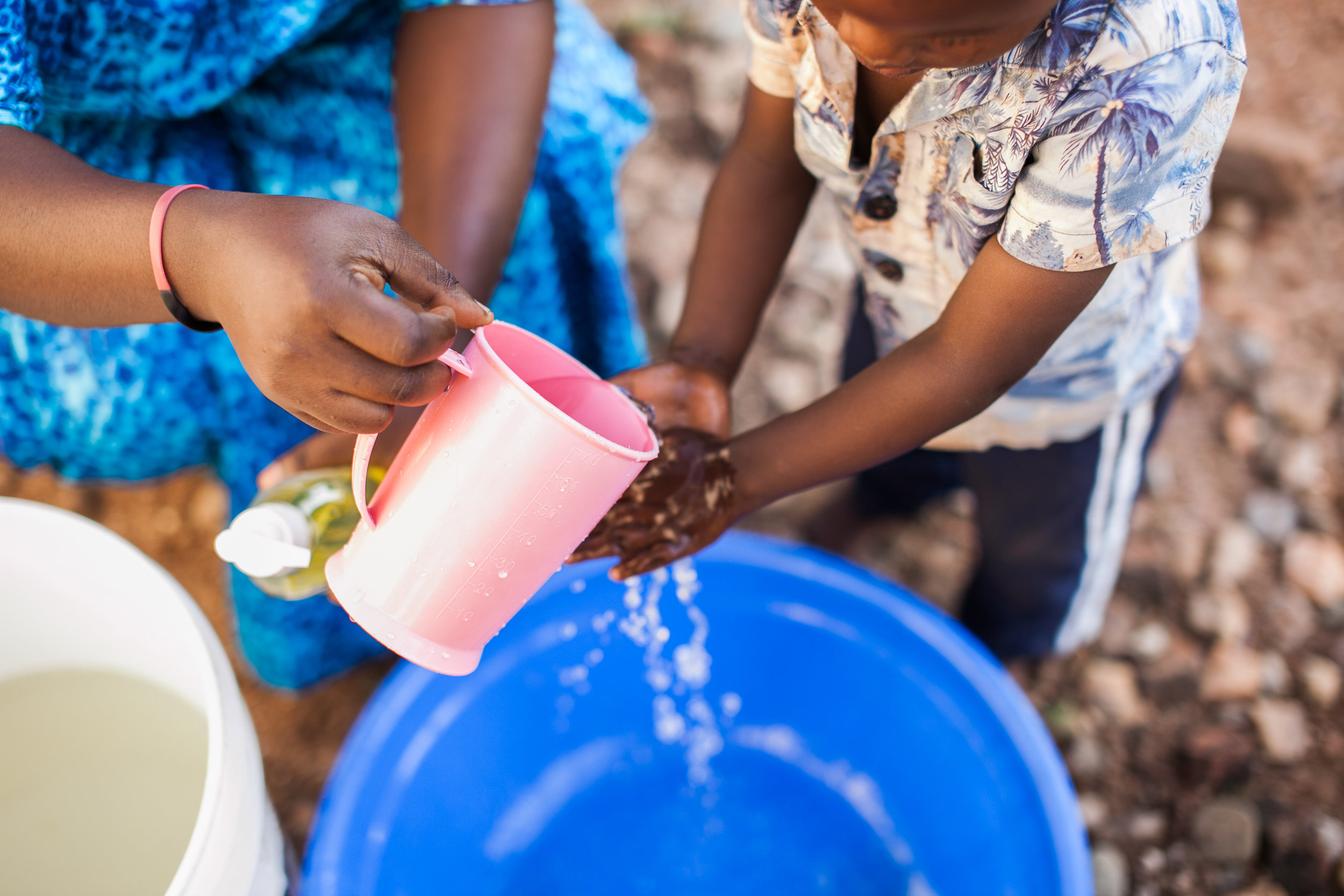Students at Mango Tree School practice handwashing with soap and water from the water pipeline up the mountain