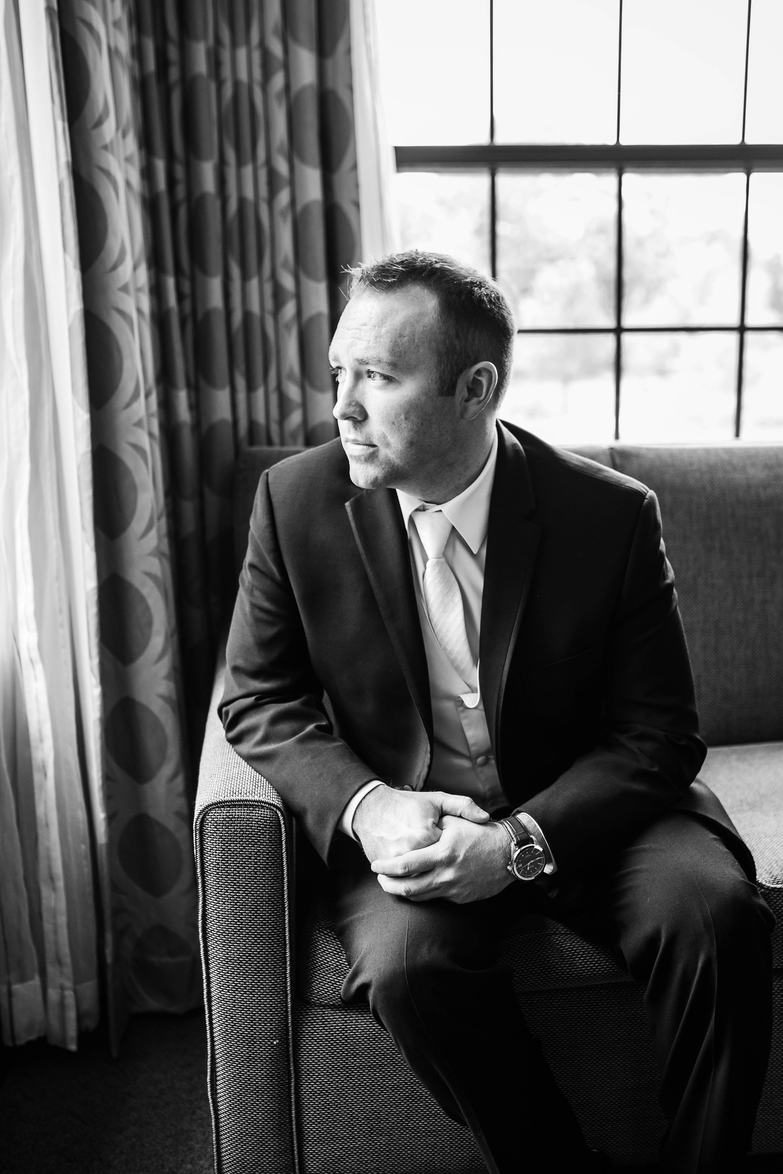 black and white portrait of groom looking out a window