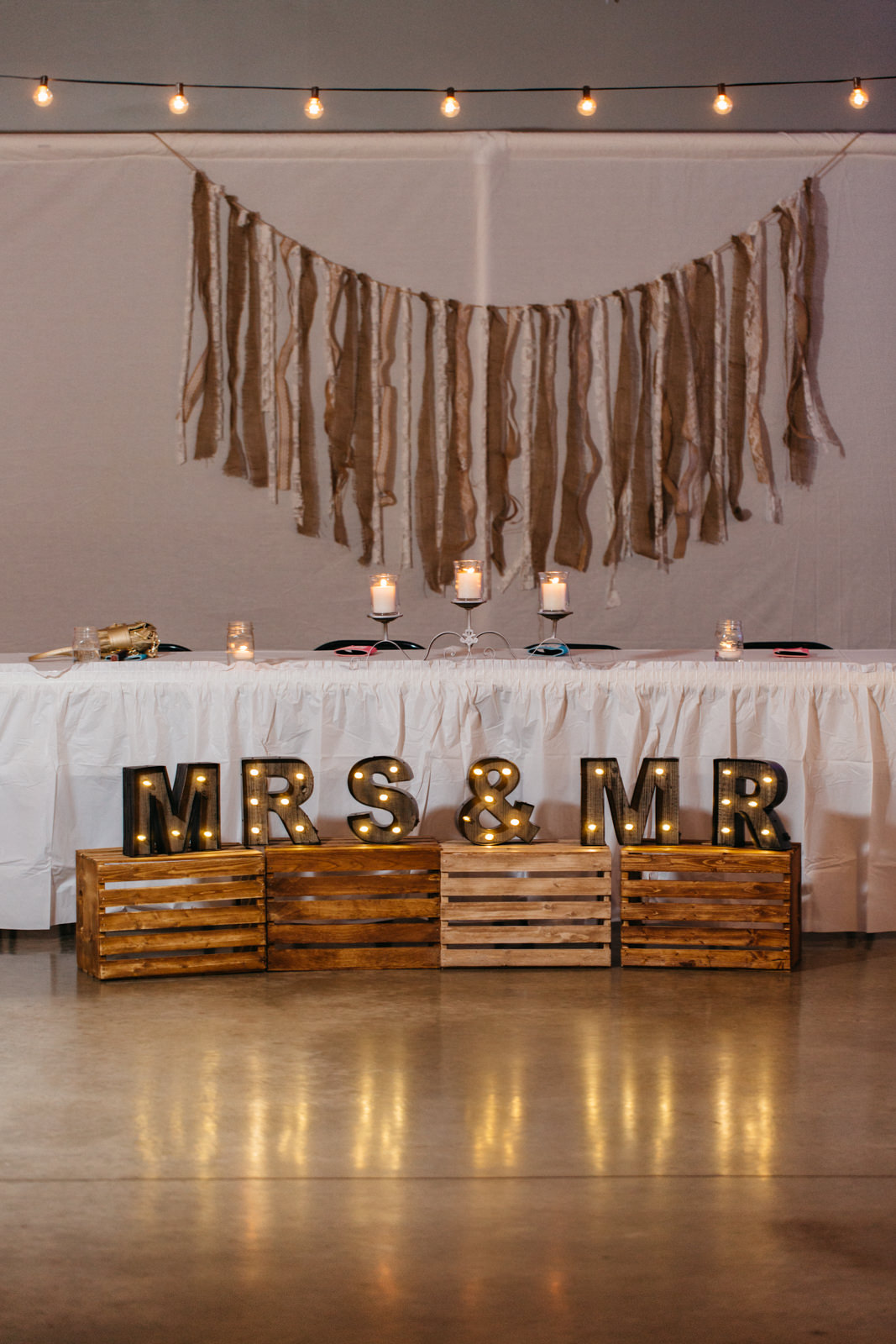 Head table decorated with rustic details at wedding reception