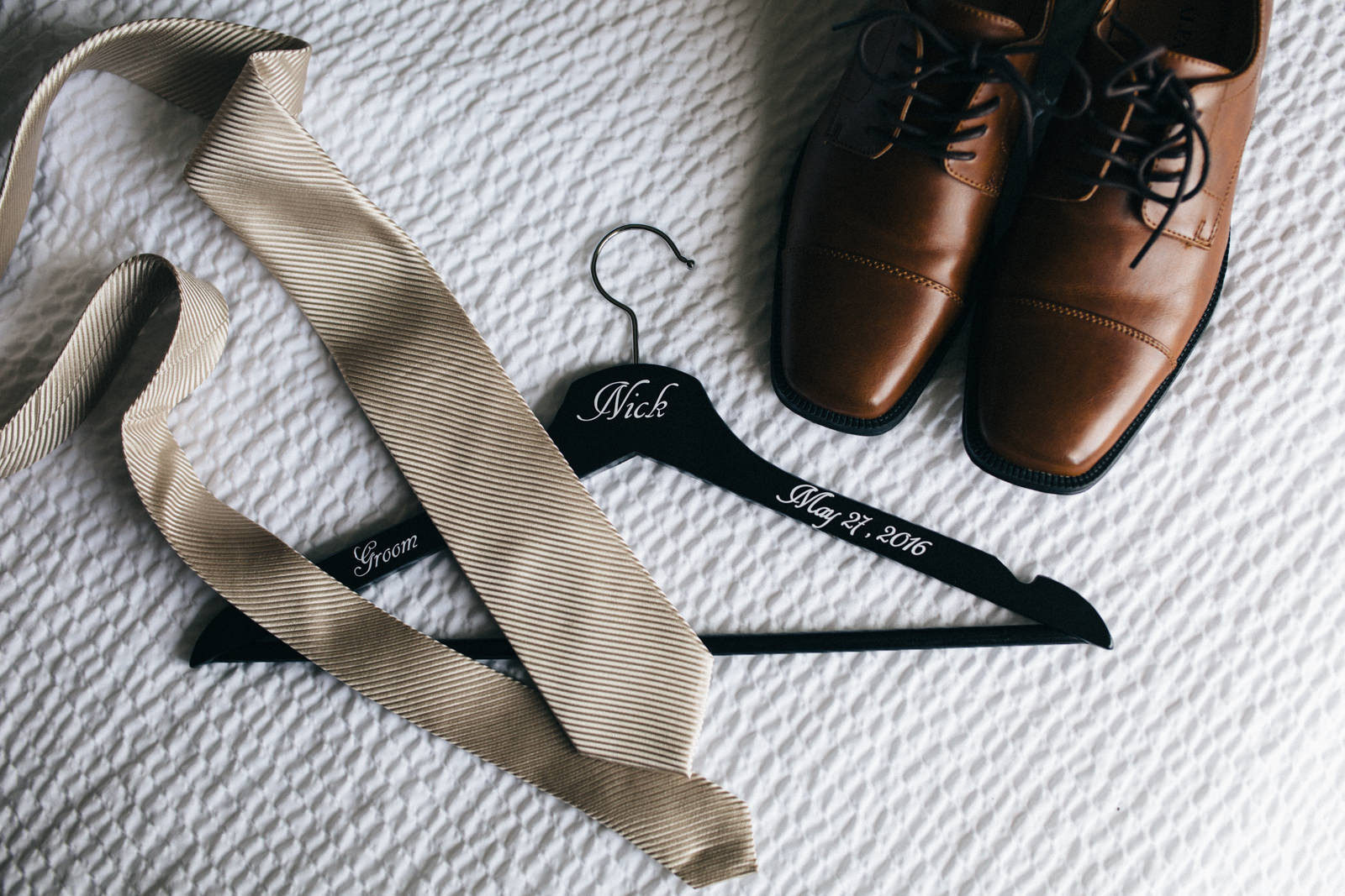 Groom's tie, suit hanger and shoes before wedding.