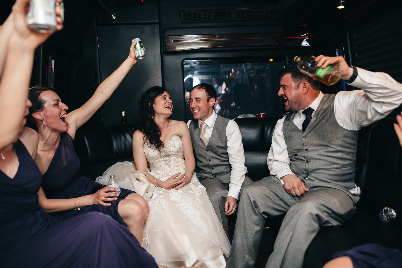 Bridal party celebrating on party bus with bride and groom.