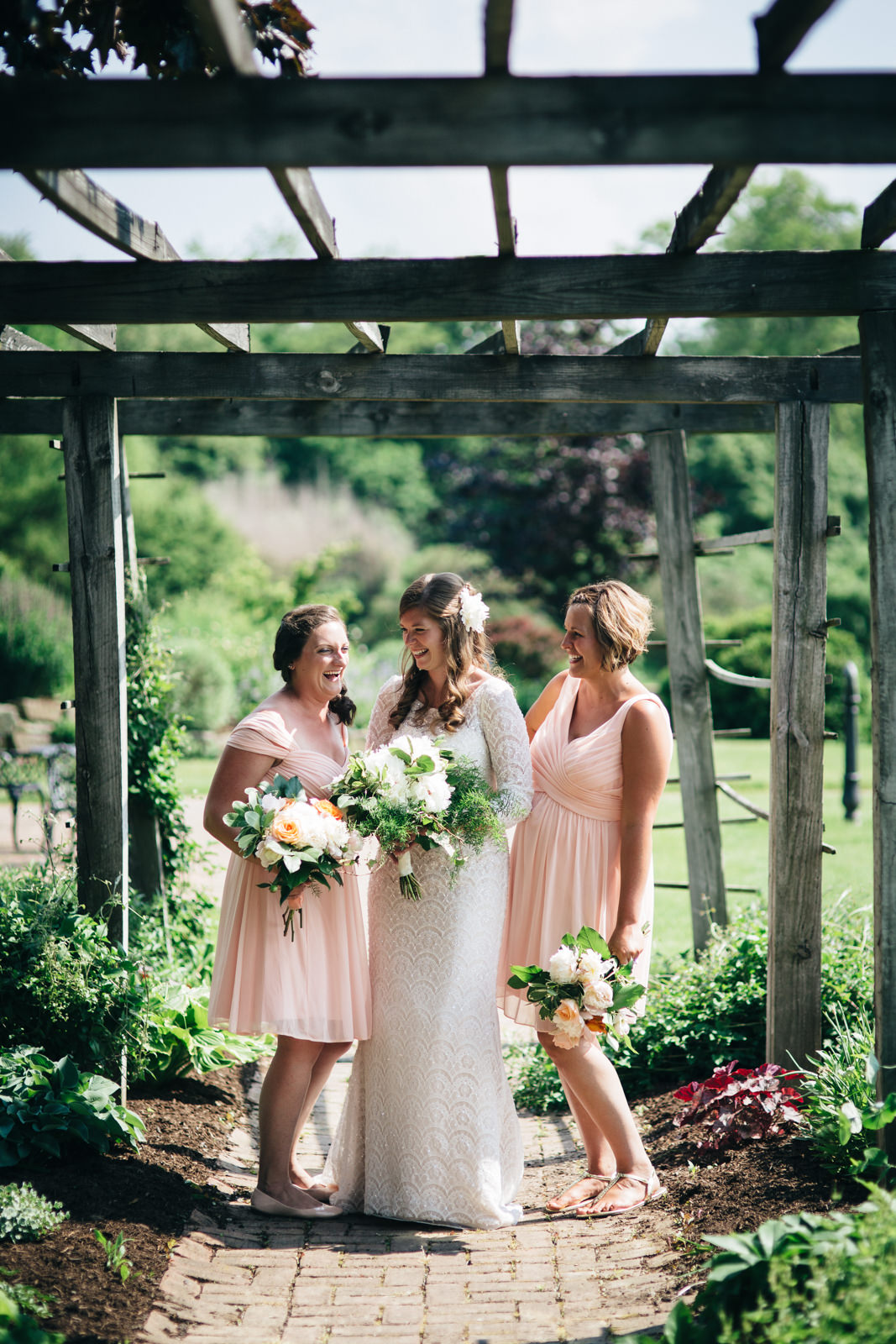 Bride and her bridesmaid smile during portrait in garden at Quailcrest Farm.