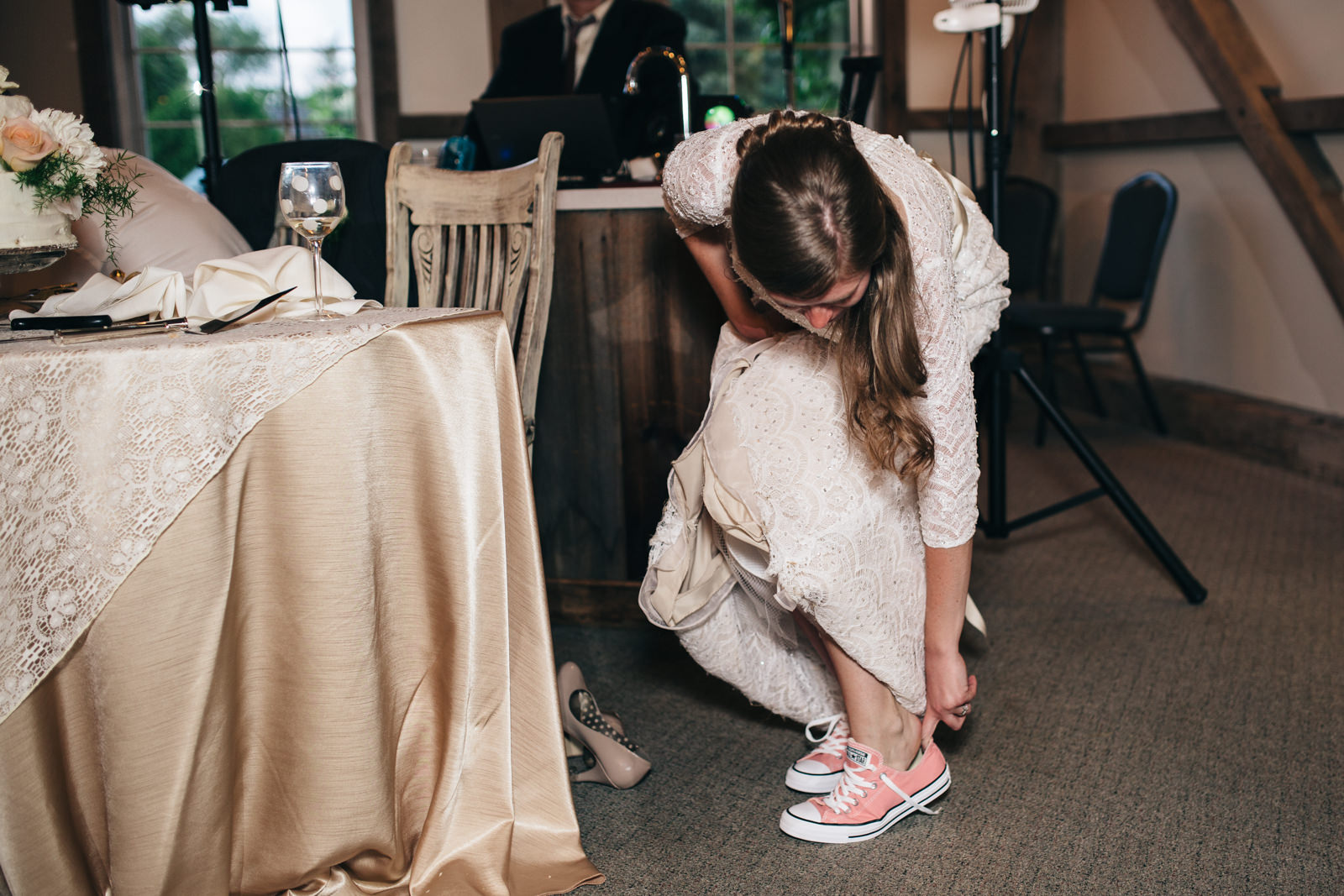 Bride puts on Converse Chuck Taylors at wedding reception.