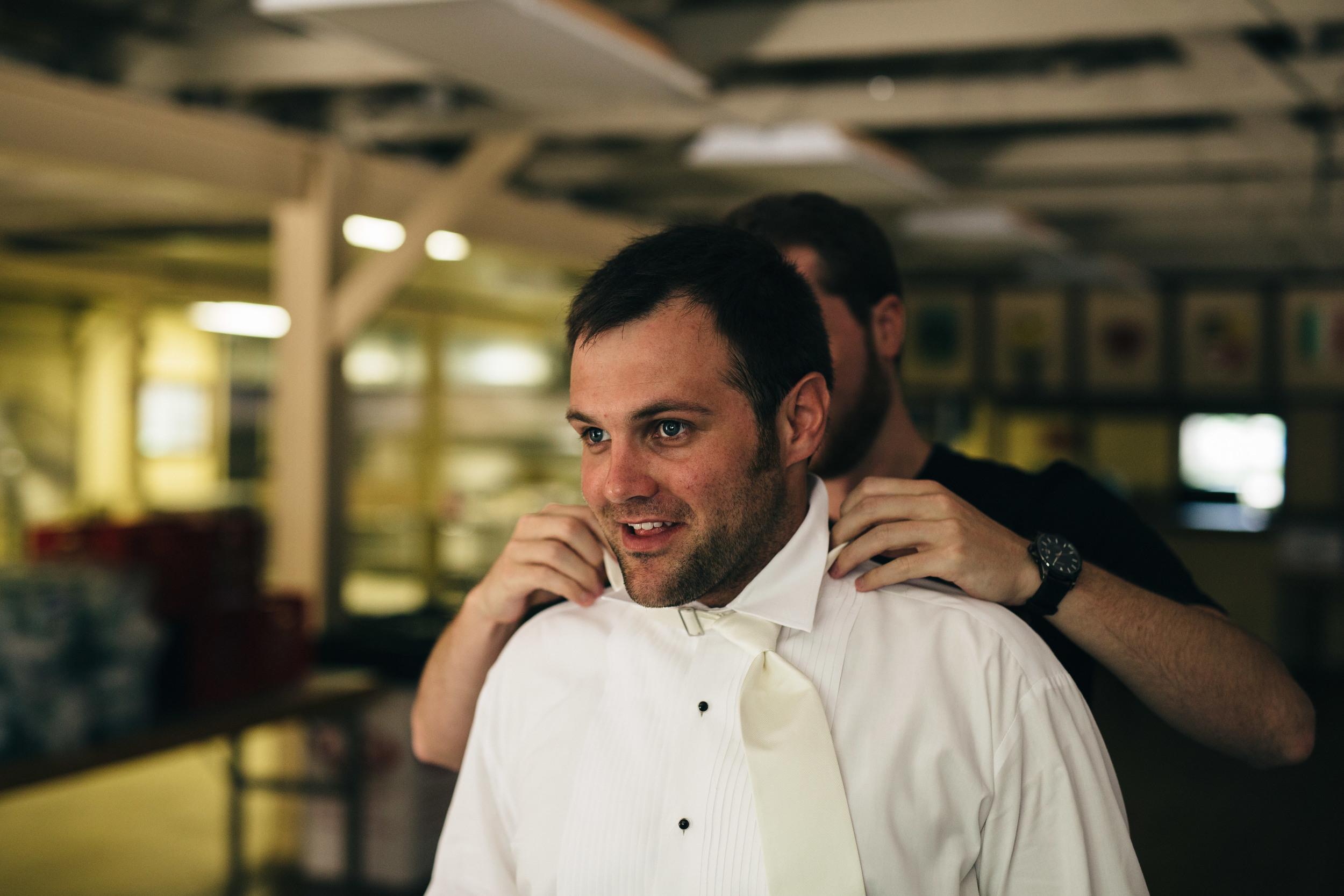 Groom getting dressed before wedding at Oak Shade Grove.