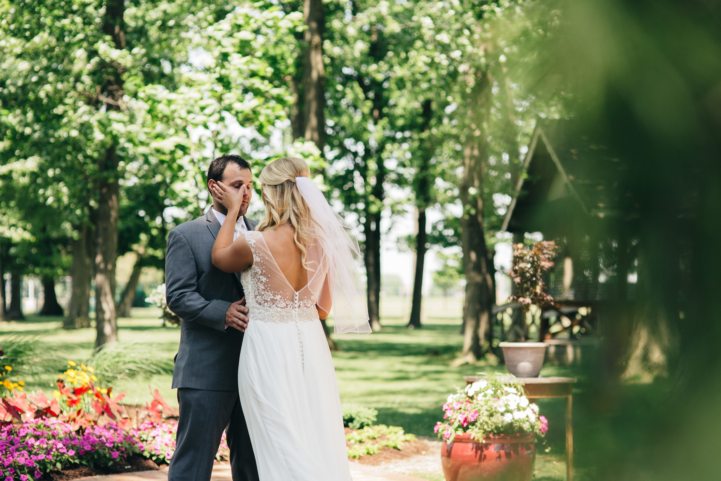 Groom gets emotional during first look with his bride during summer wedding.