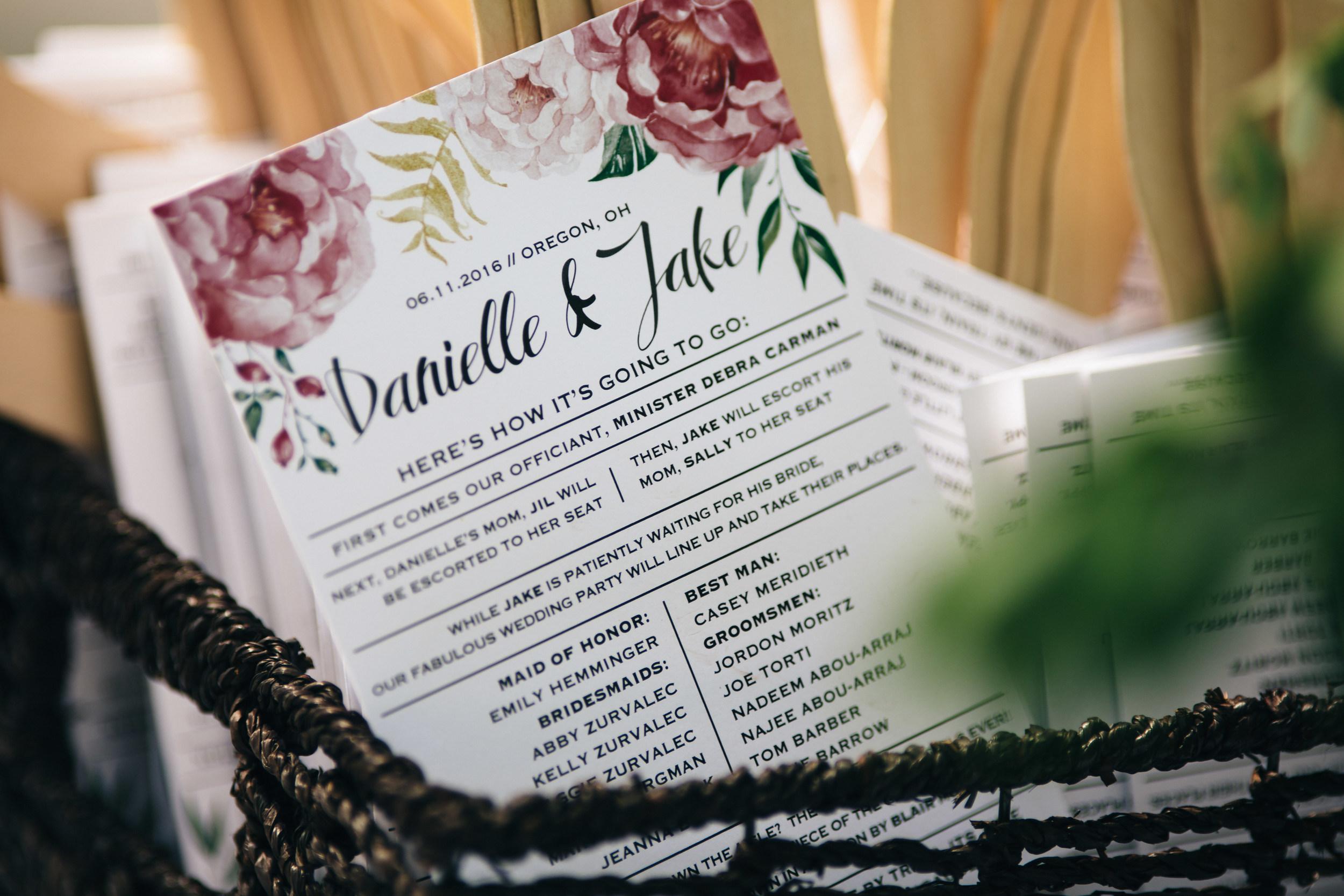 Floral design on wedding program fans at summer wedding.
