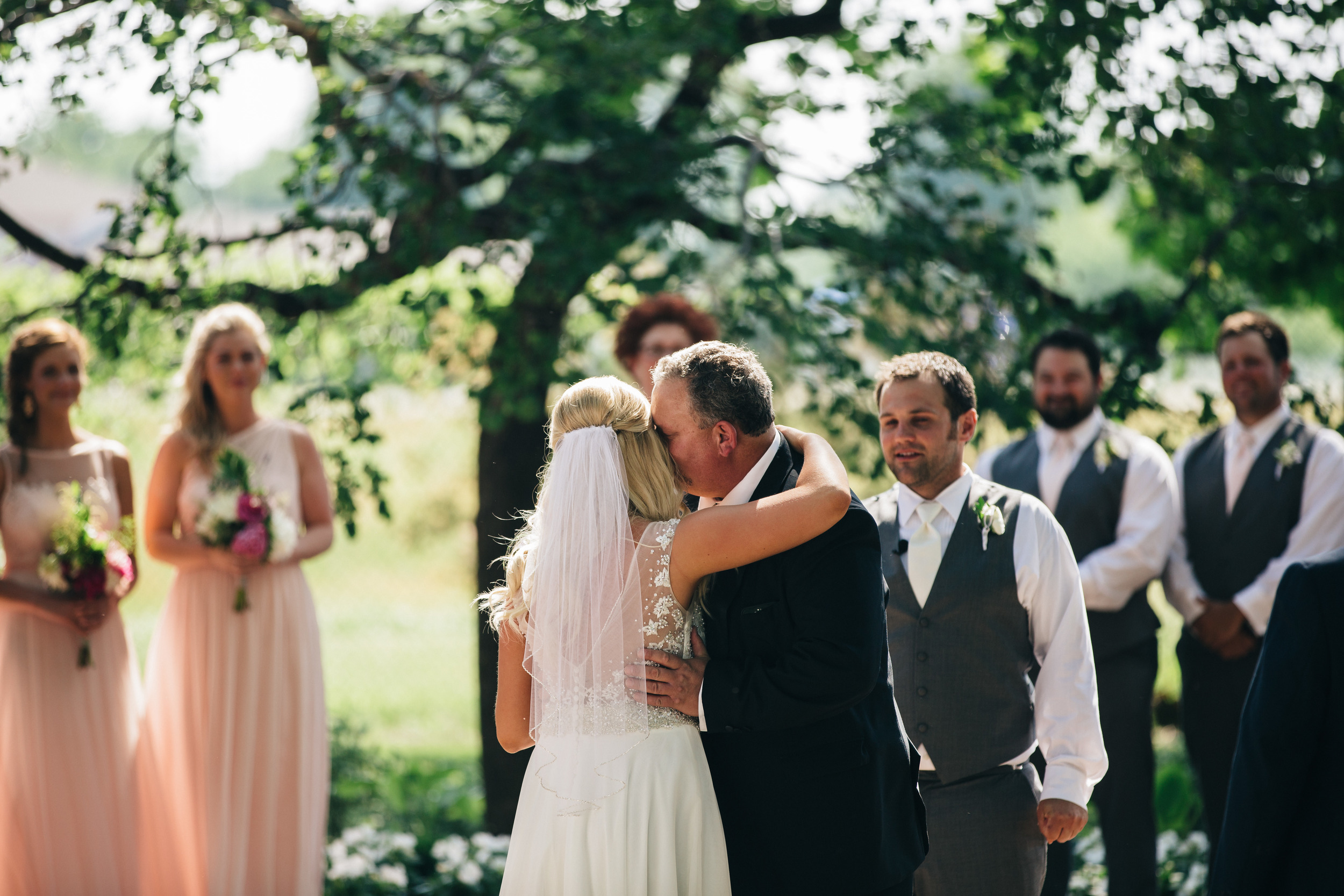 Brides father gives her away during outdoor wedding ceremony in Toledo, Ohio.