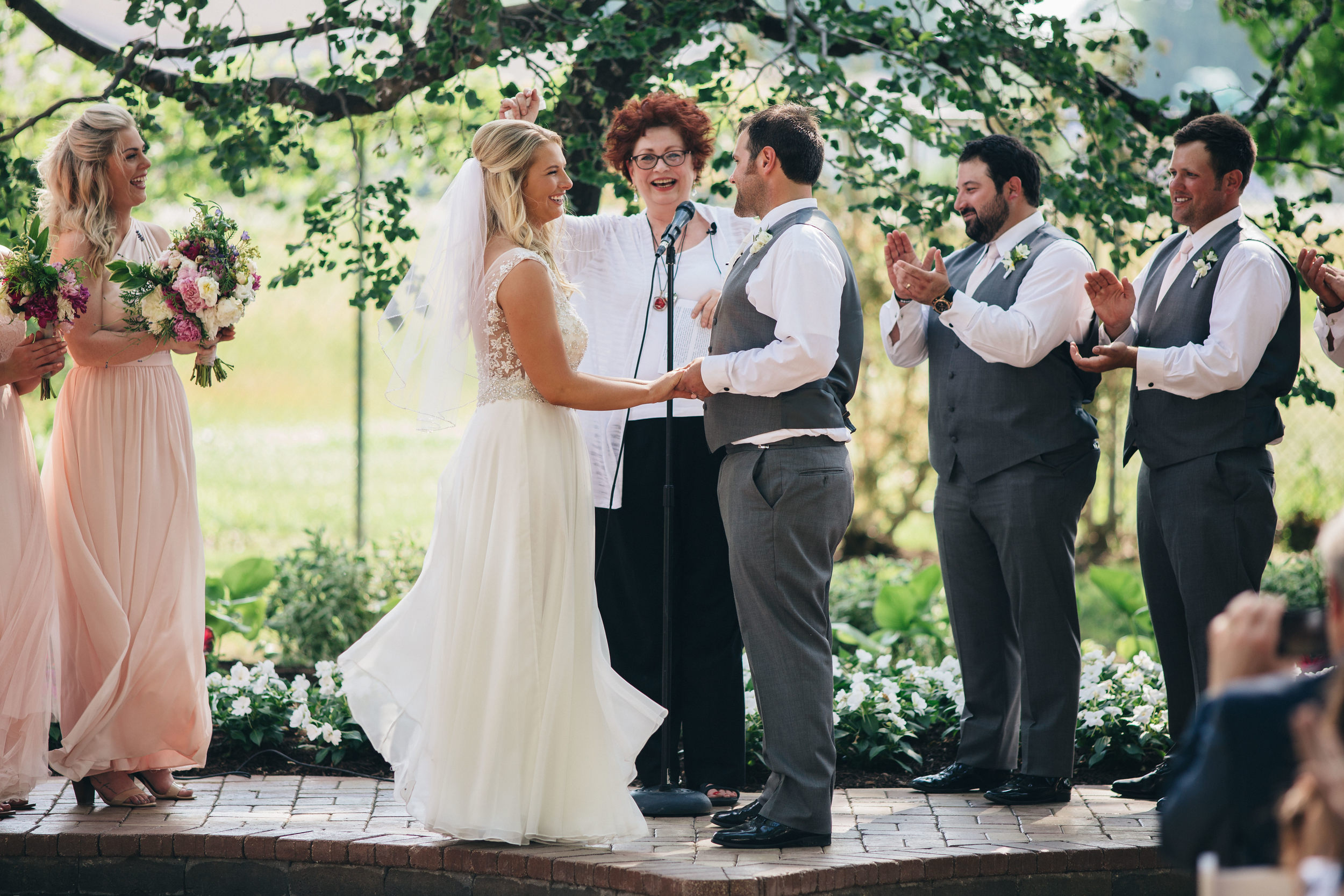 Bride and groom at altar in outdoor summer wedding.