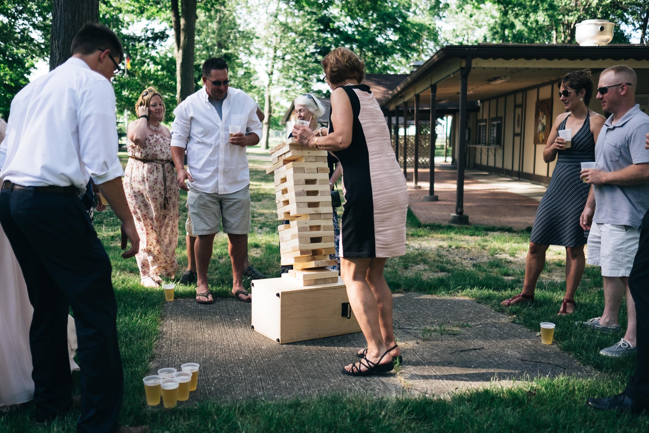 Wedding guests play outdoor games at wedding reception.
