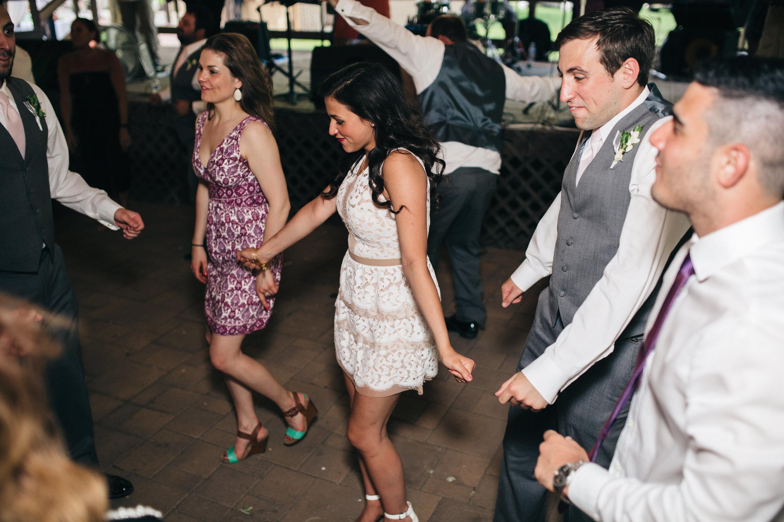 Wedding guests dancing to wedding band at reception.