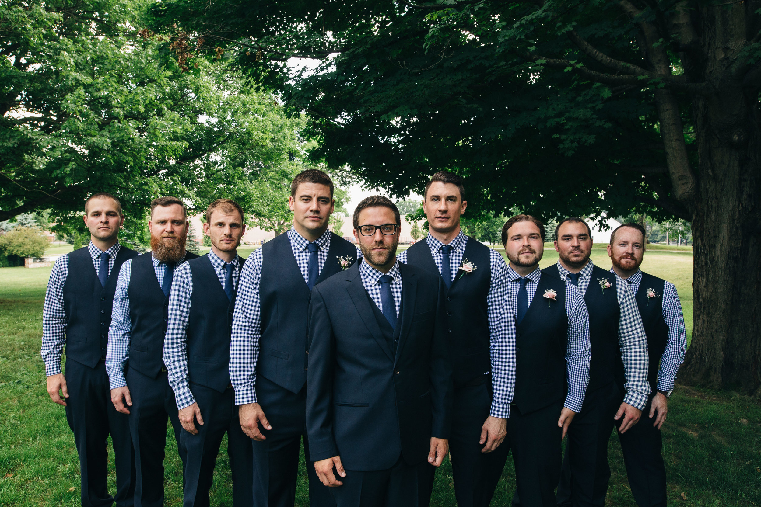 Stylish groomsmen in navy blue and checkered dress shirts in Canton, Ohio.