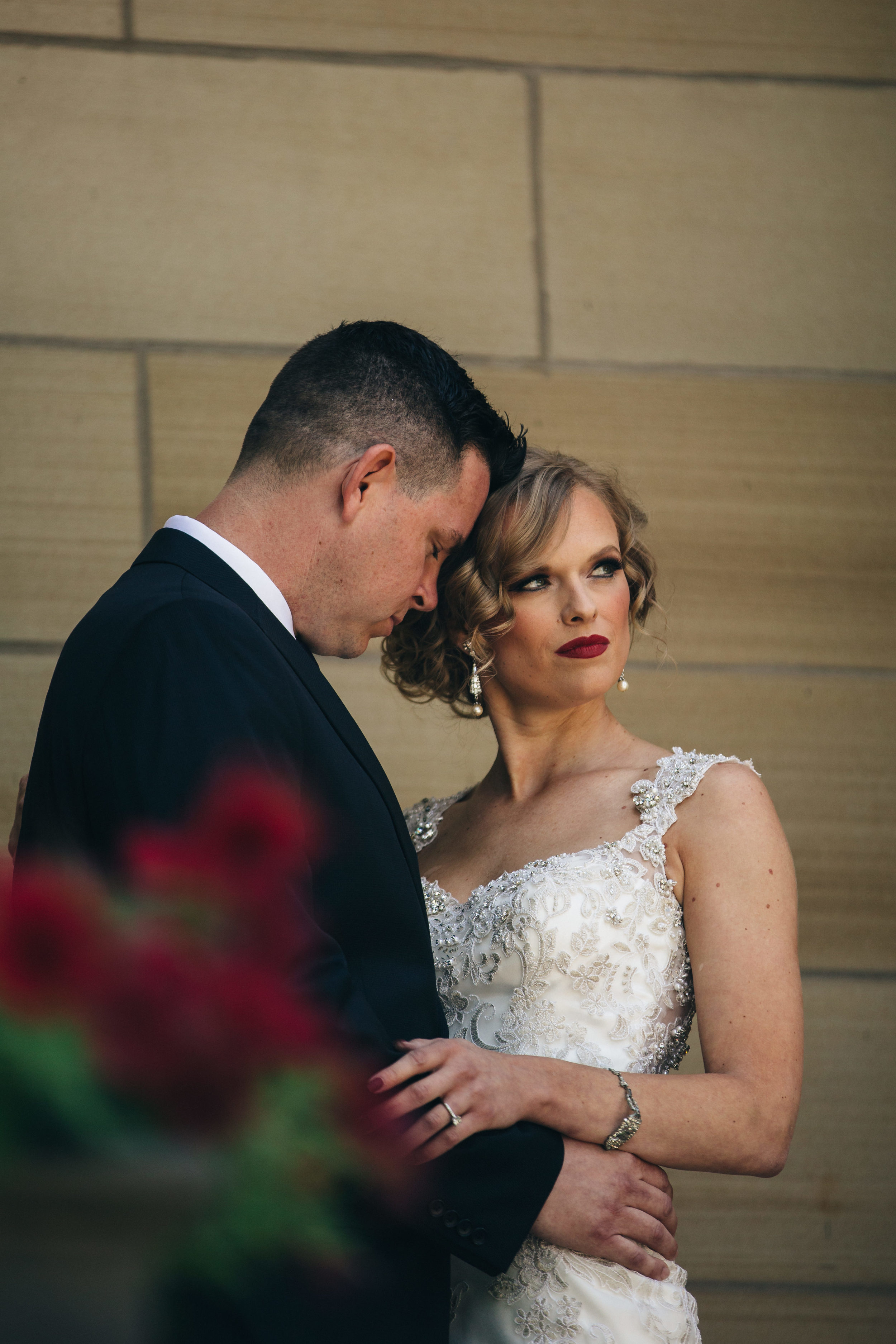 Beautiful bride in red lipstick with new groom.