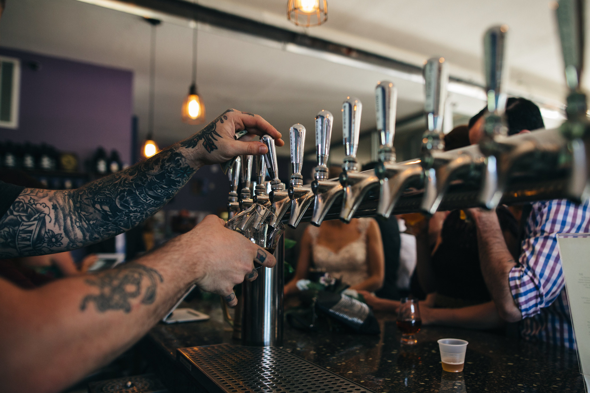 Bartender serves beer to bride at Catawba Island Brewery.