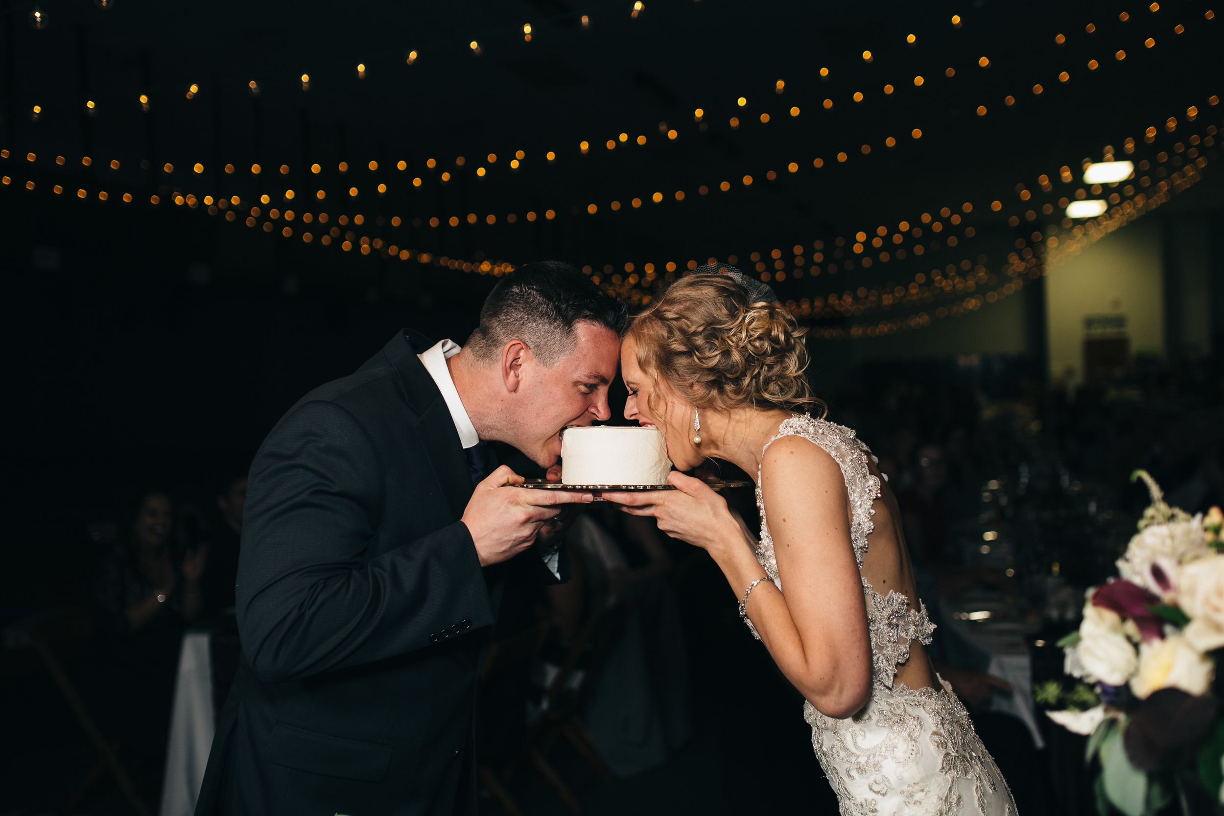 Bride and groom cut cake at wedding reception in Fremont, Ohio.