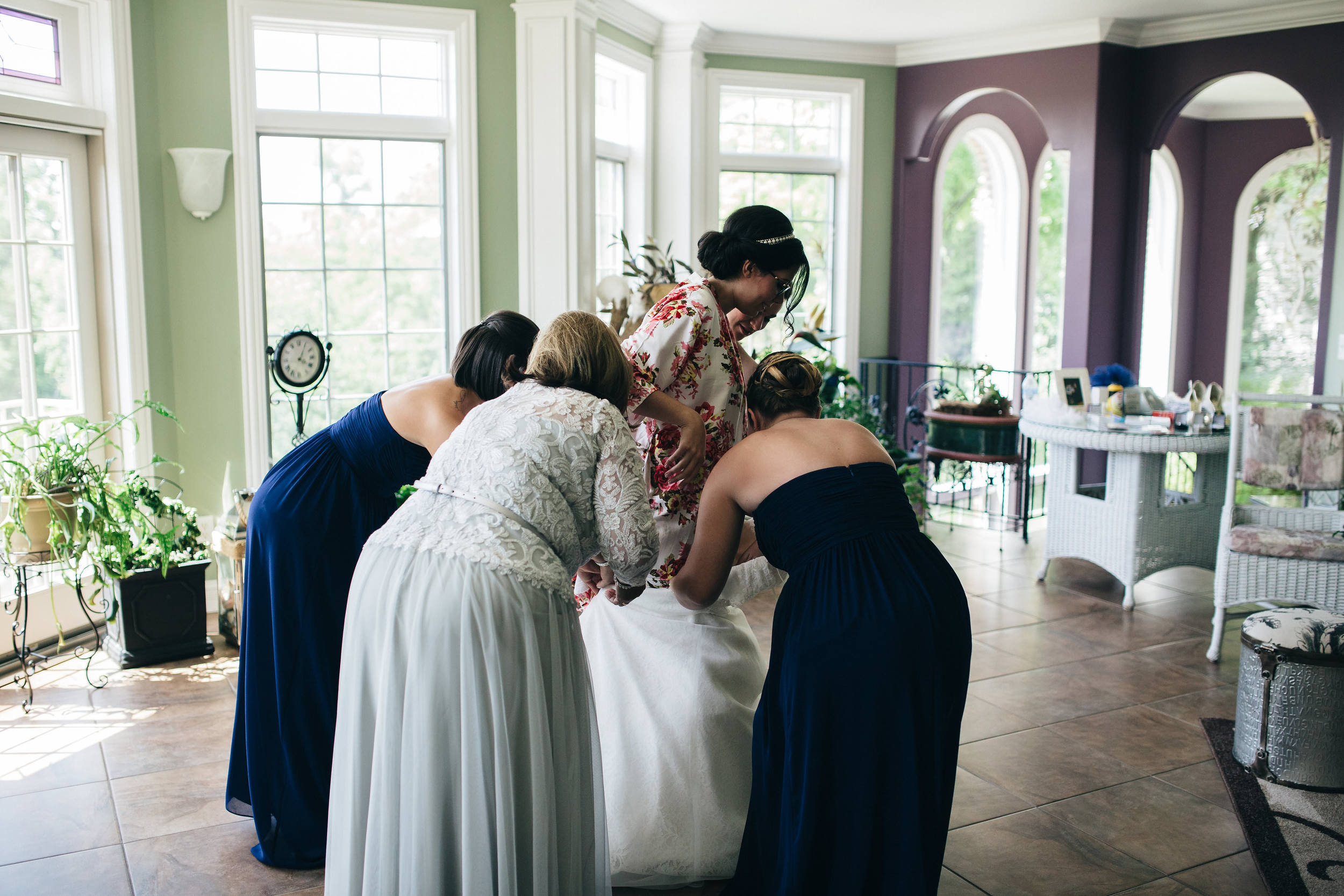 Bride stepping into wedding gown at home in Maumee, Ohio.